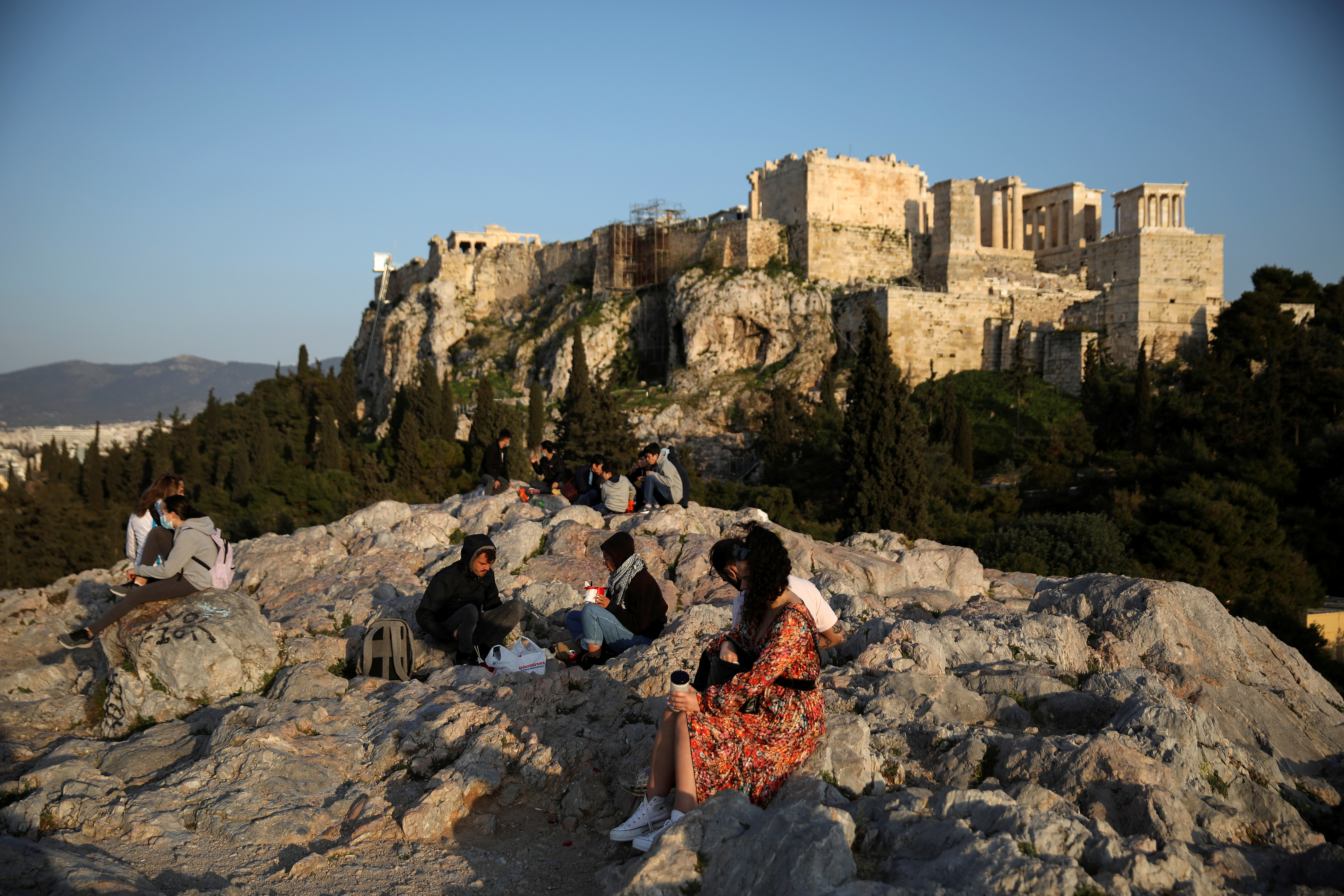 FILE  PHOTO: People visit the Areios Pagos hill, with the Acropolis' Propylaea seen in the background, amid the coronavirus disease (COVID-19) pandemic, in Athens, Greece, March 10, 2021. Picture taken March 10, 2021. REUTERS/Louiza Vradi