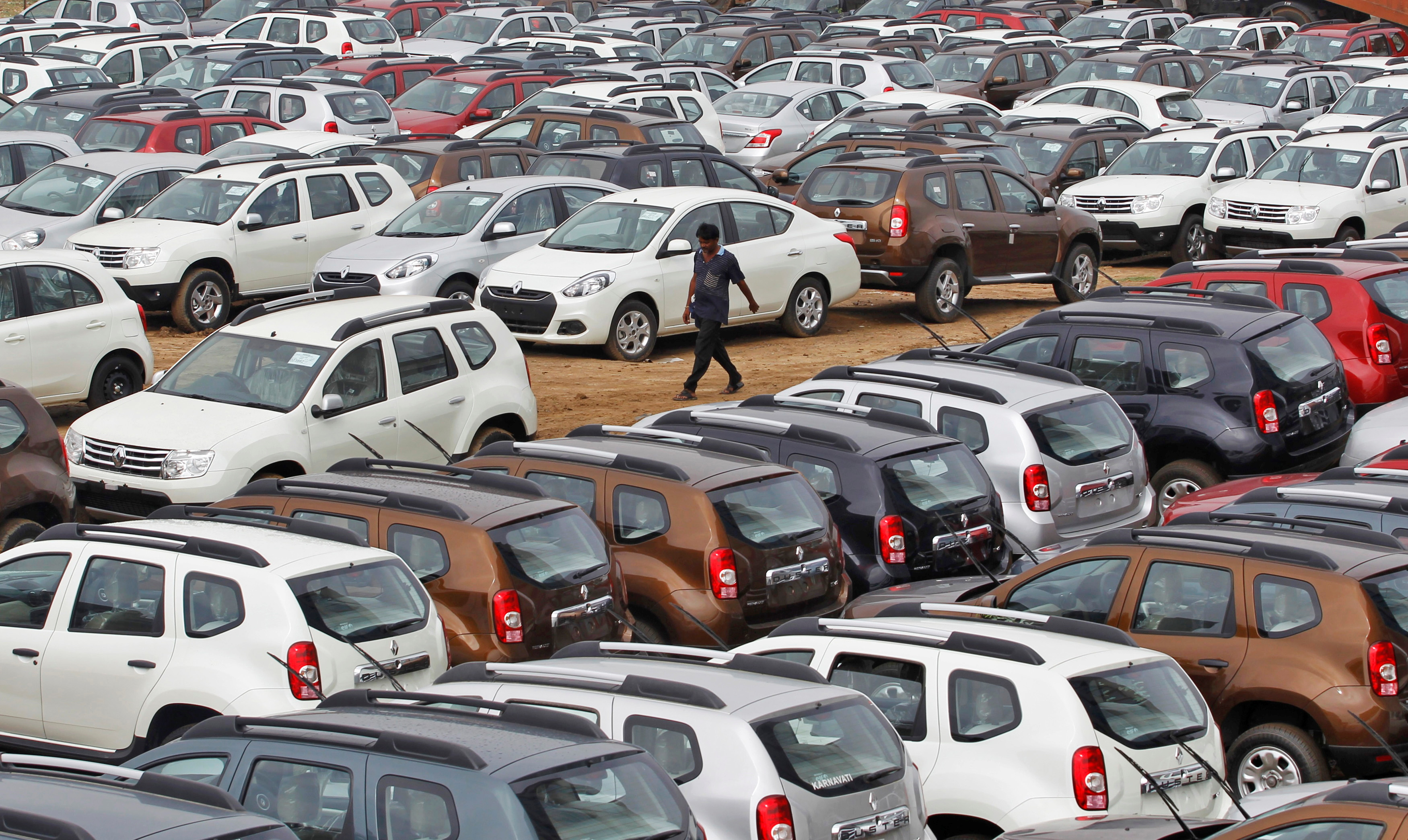 A worker walks past parked Renault cars at its stockyard on the outskirts of the western Indian city of Ahmedabad June 11, 2013. REUTERS/Amit Dave