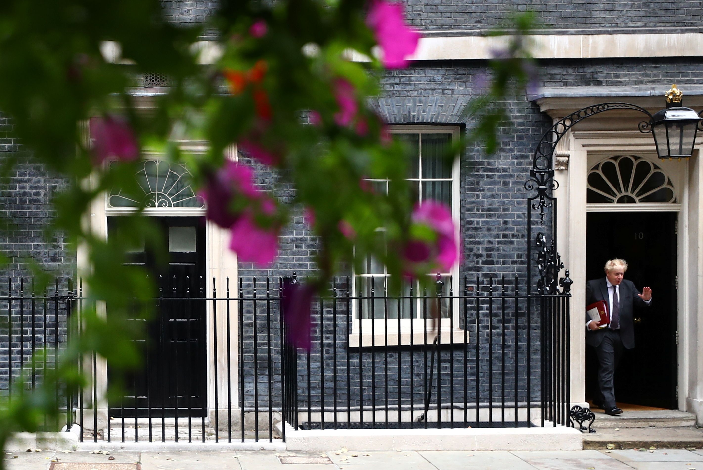 Britain's Prime Minister Boris Johnson gestures as he walks outside Downing Street in London, Britain, September 15, 2021. REUTERS/Hannah McKay