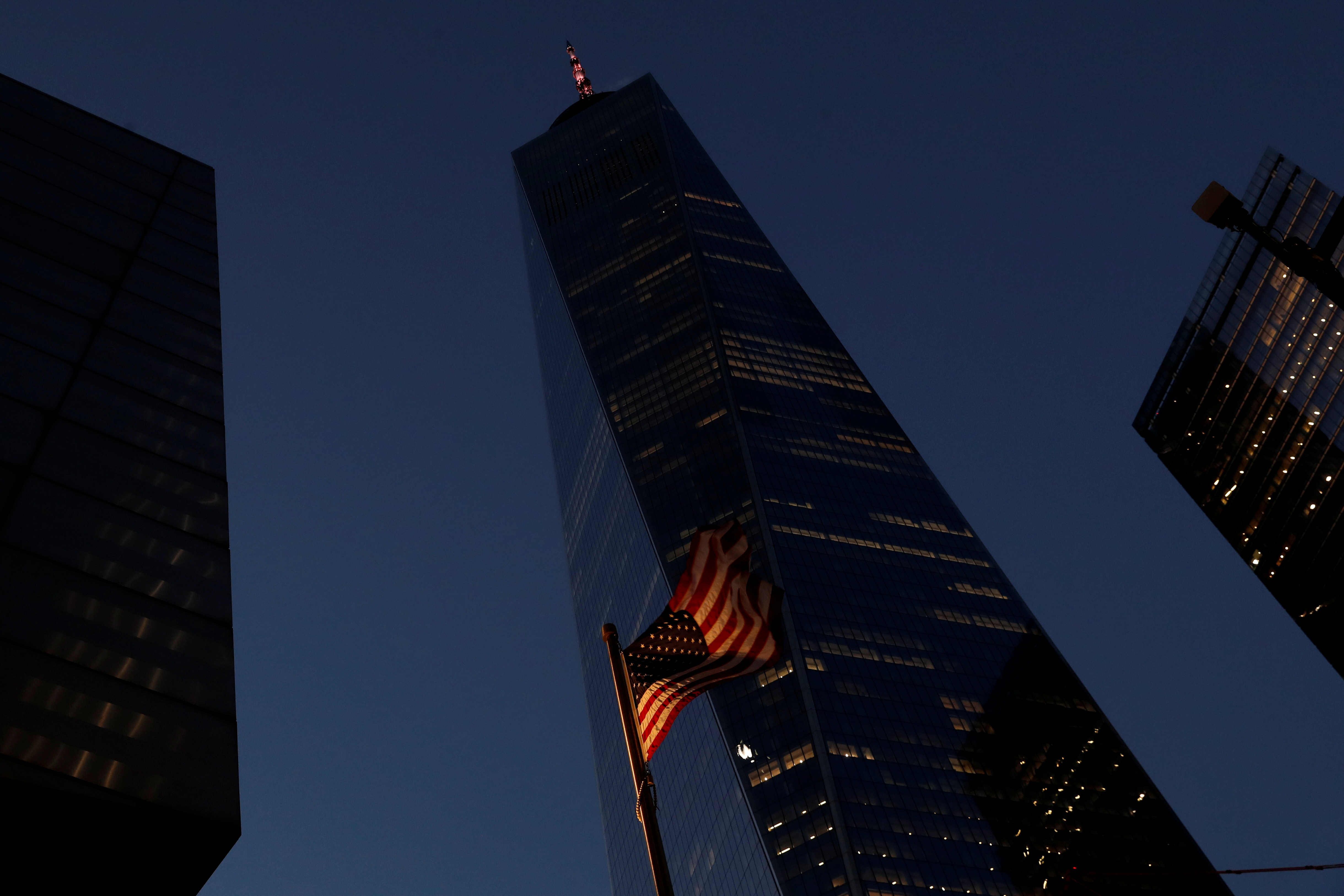 The One World Trade Center building is illuminated in red to honor the lives lost to the coronavirus disease (COVID-19) as the U.S. flag blows in the wind in the Manhattan borough of New York, U.S., January 19, 2021. REUTERS/Shannon Stapleton