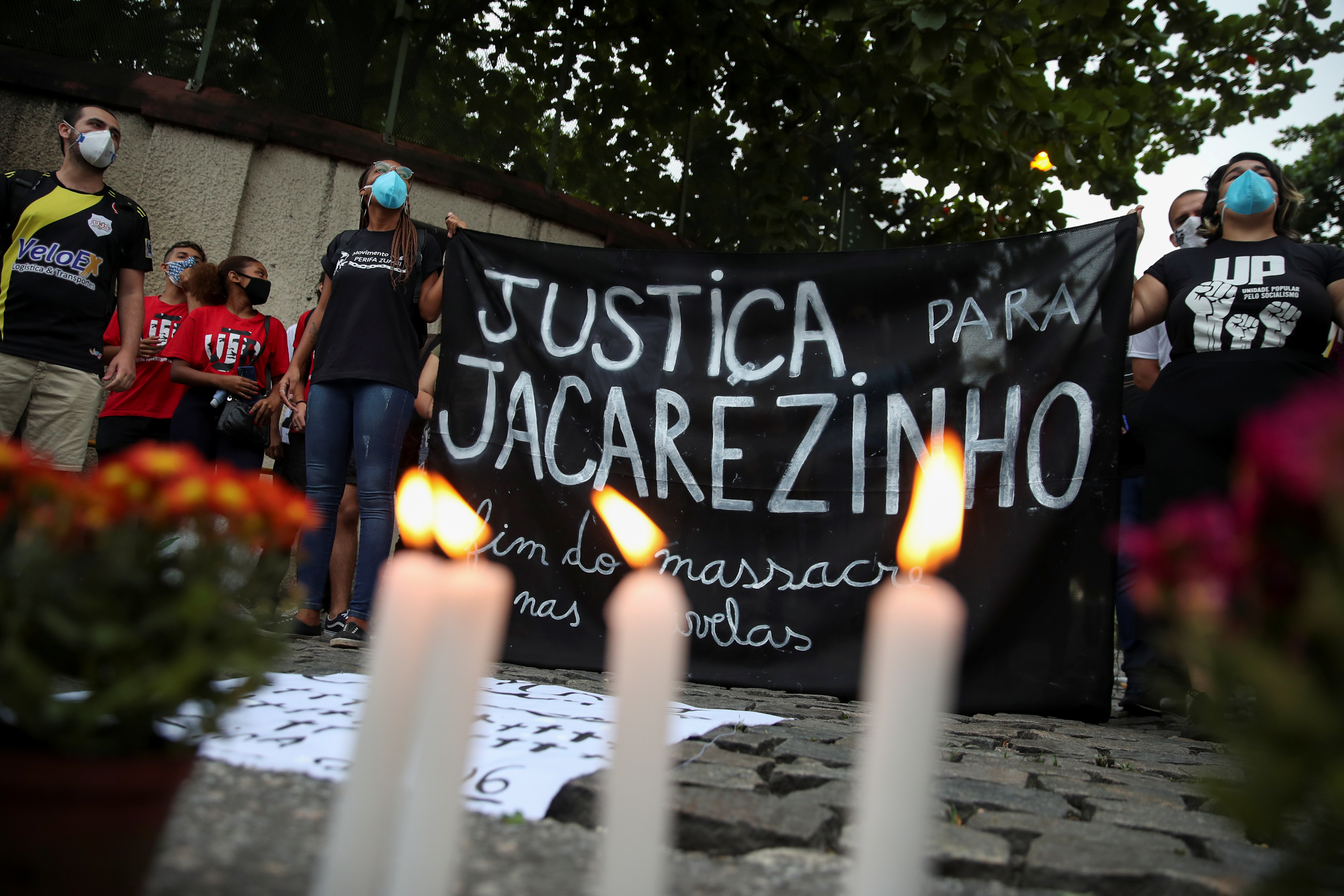 People attend a protest against police violence outside Jacarezinho slum after a police operation which resulted in 25 deaths in Rio de Janeiro, Brazil, May 7, 2021. Banner reads:
