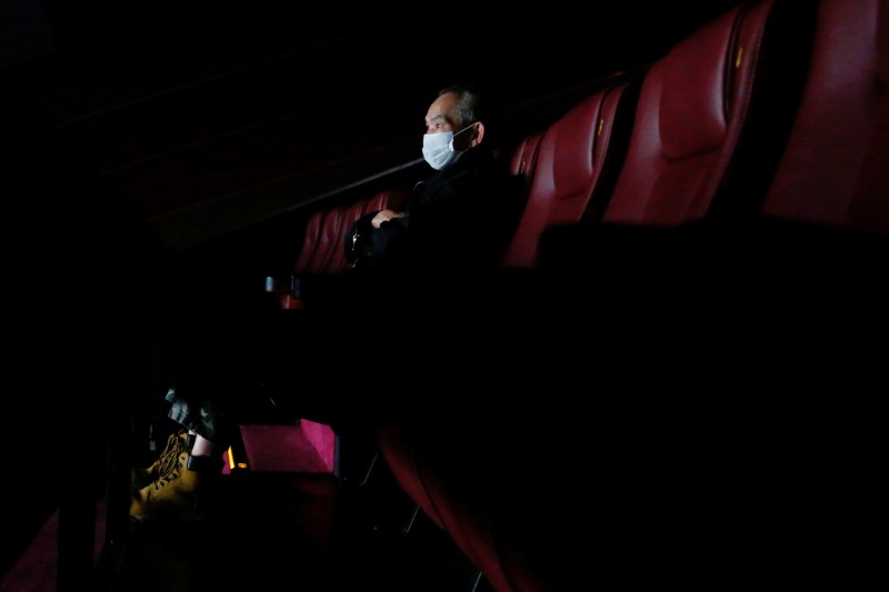 A man wears protective mask as he watches a movie, following the outbreak of the new coronavirus, in Hong Kong, China February 10, 2020. REUTERS/Tyrone Siu