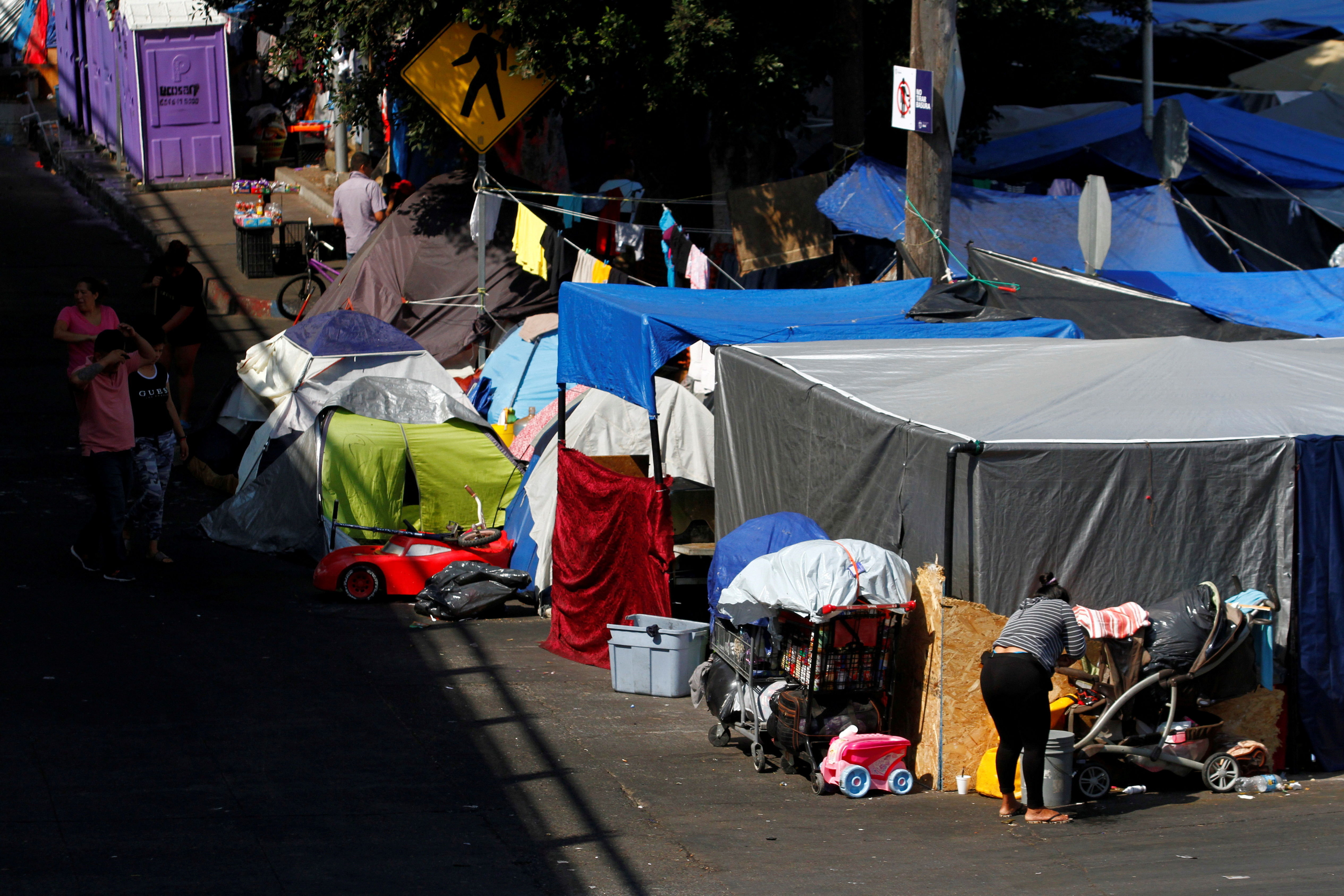Asylum-seeking migrants are pictured at a makeshift camp after the U.S. Supreme Court ordered to uphold an immigration policy implemented under former President Donald Trump that forced thousands of asylum seekers to stay in Mexico to await U.S. hearings, at El Chaparral crossing port with the U.S., in Tijuana, Mexico August 25, 2021. REUTERS/Jorge Duenes/