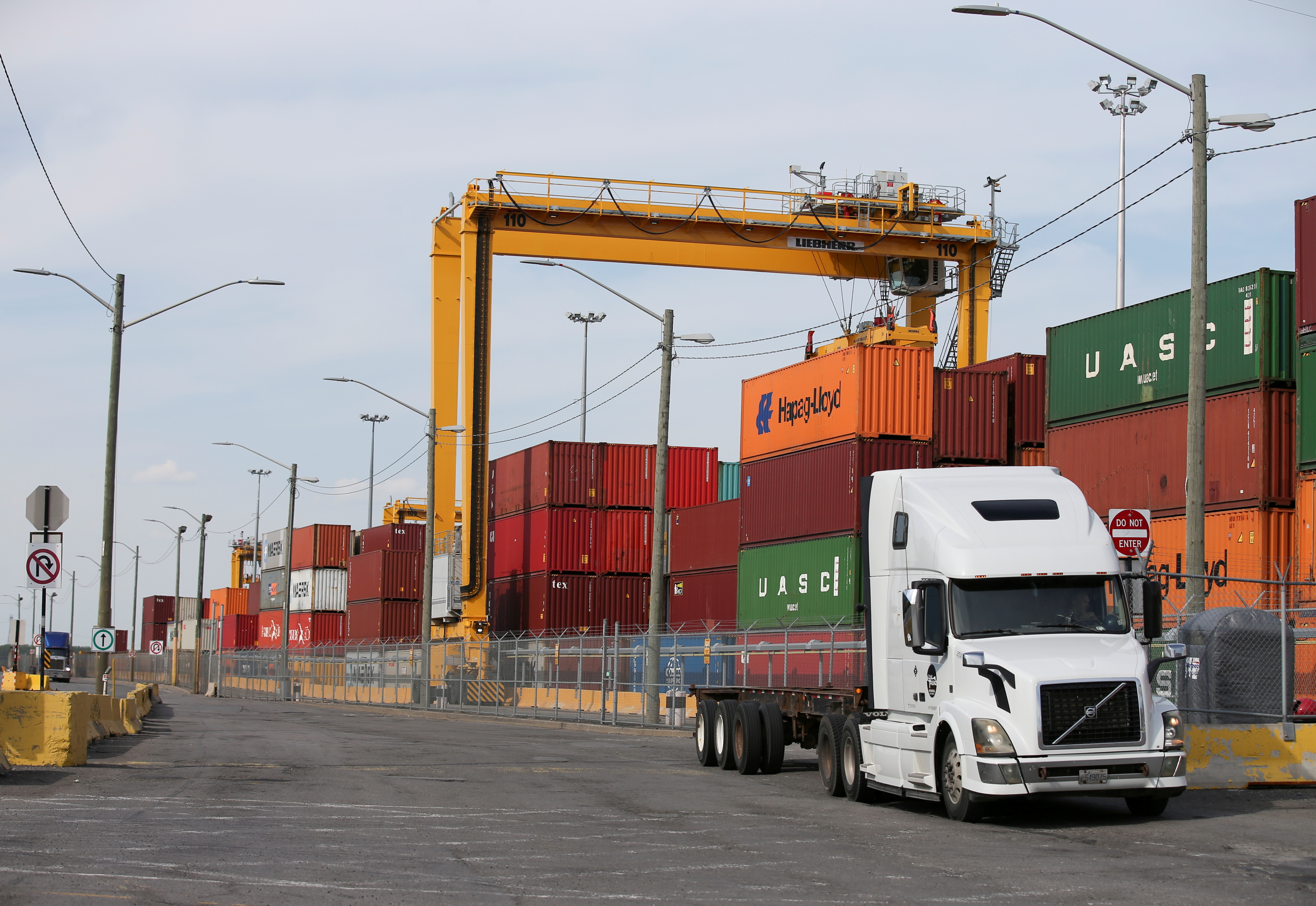 A truck moves past stacked shipping containers at the Port of Montreal in Montreal, Quebec, Canada, May 17, 2021.  REUTERS/Christinne Muschi