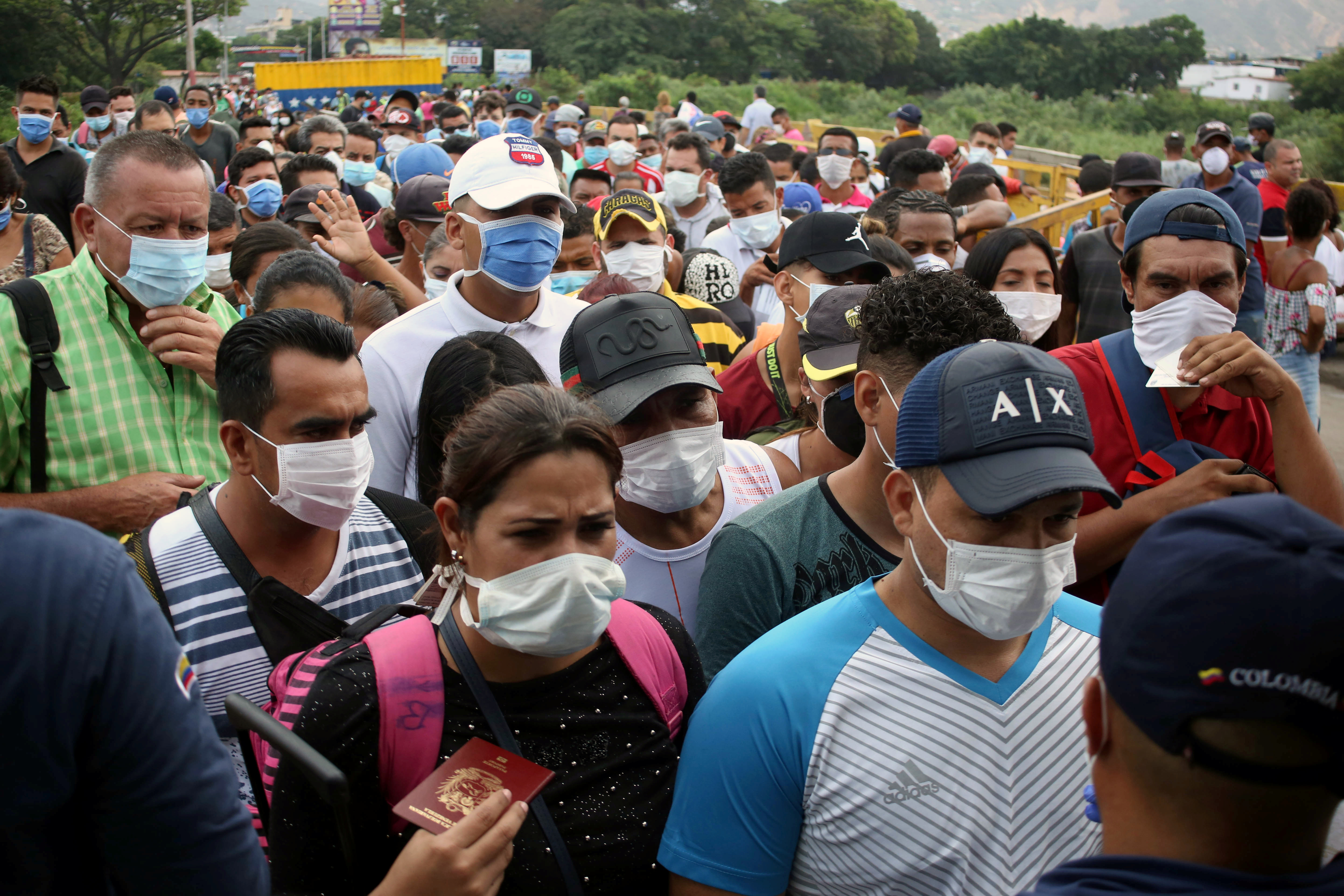 People wearing protective face masks line up to cross the border between Colombia and Venezuela at the Simon Bolivar international bridge, after the World Health Organization has described the outbreak as a pandemic, in Cucuta, Colombia March 12, 2020.  REUTERS/Carlos Eduardo Ramirez