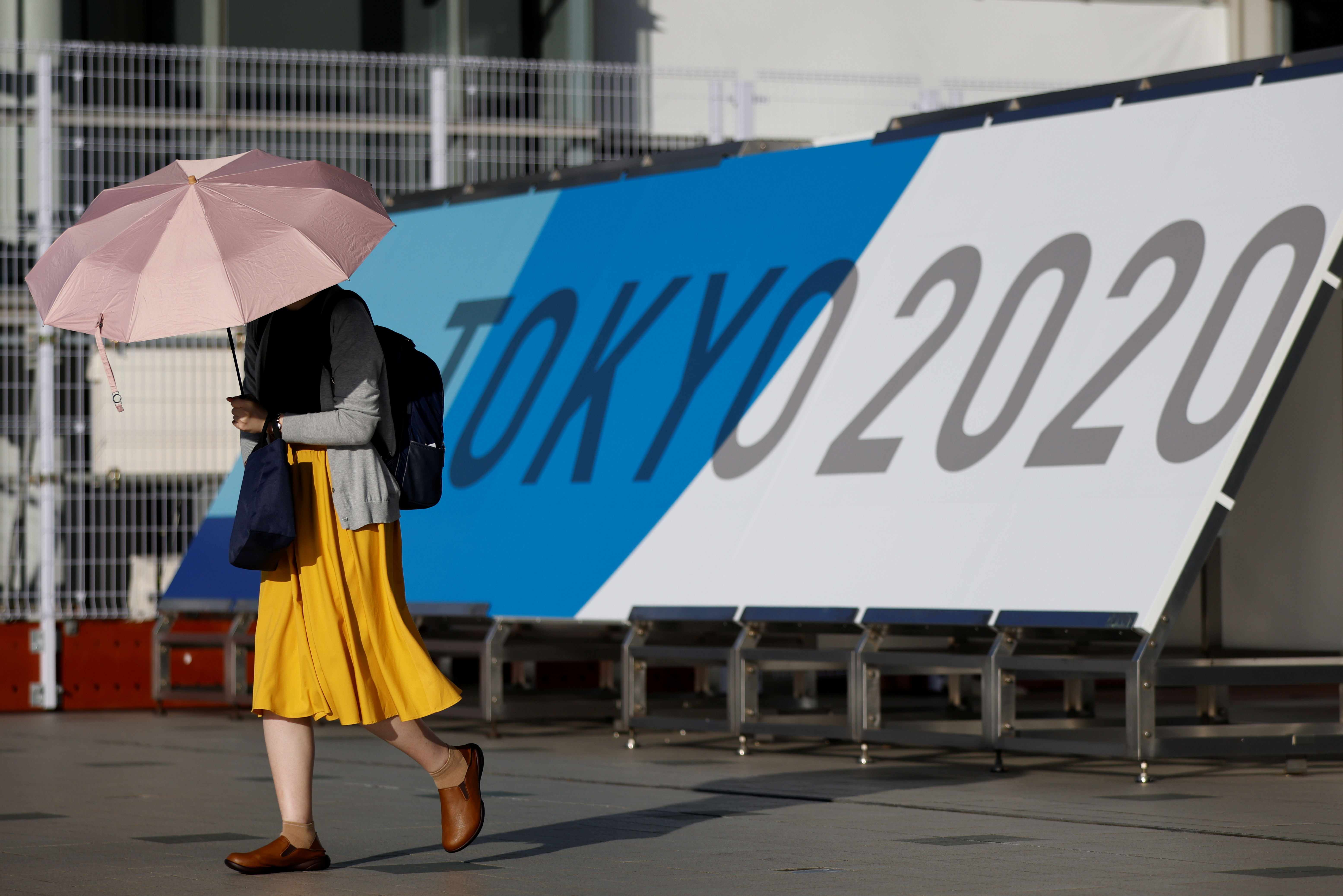 A woman walks past Tokyo 2020 Olympic Games signage at the Main Press Center during the coronavirus disease (COVID-19) outbreak in Tokyo, Japan, July 16, 2021.  REUTERS/Thomas Peter