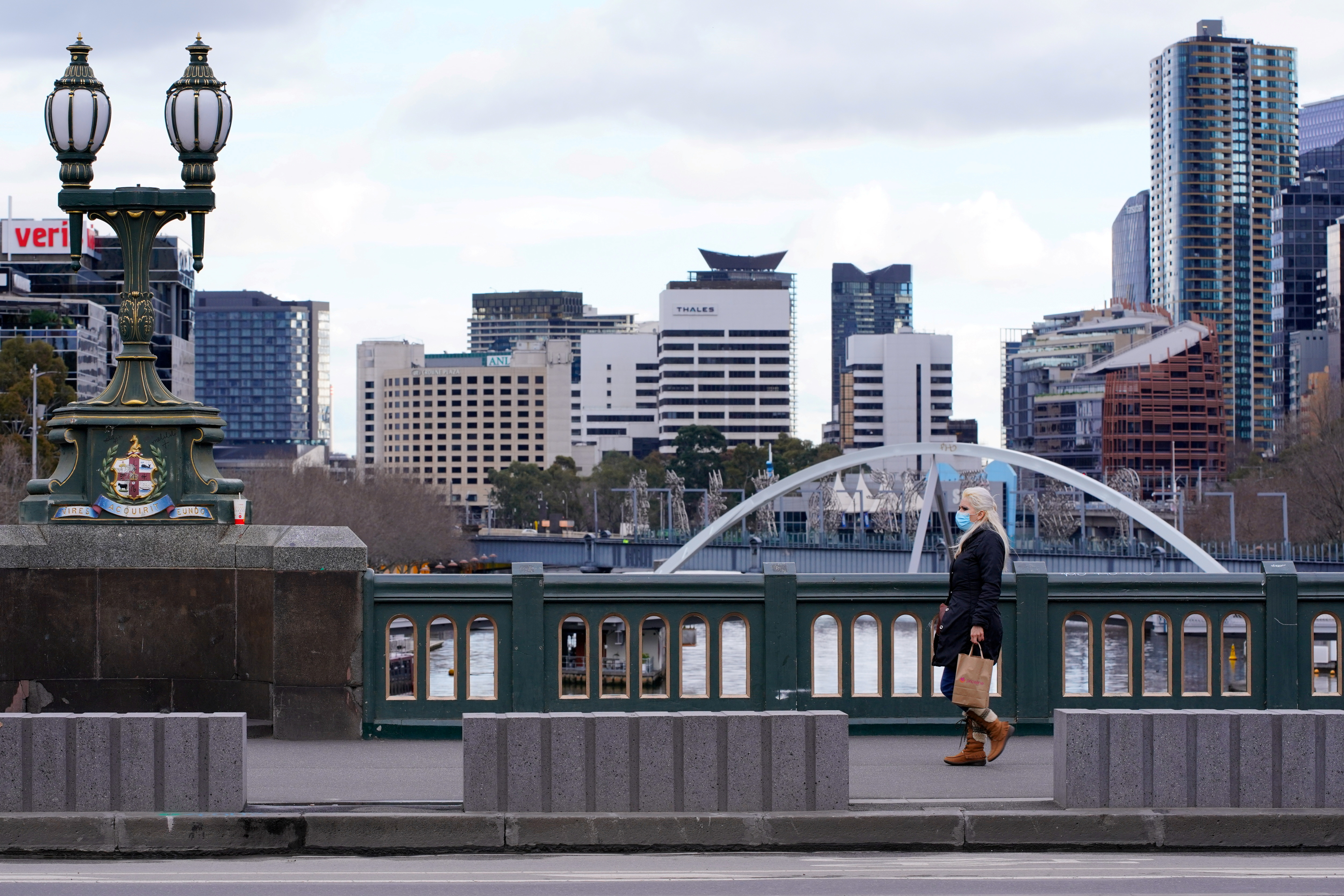 A lone woman, wearing a protective face mask, walks across a city centre bridge as the state of Victoria looks to curb the spread of a coronavirus disease (COVID-19) outbreak in Melbourne, Australia, July 16, 2021.  REUTERS/Sandra Sanders/File Photo
