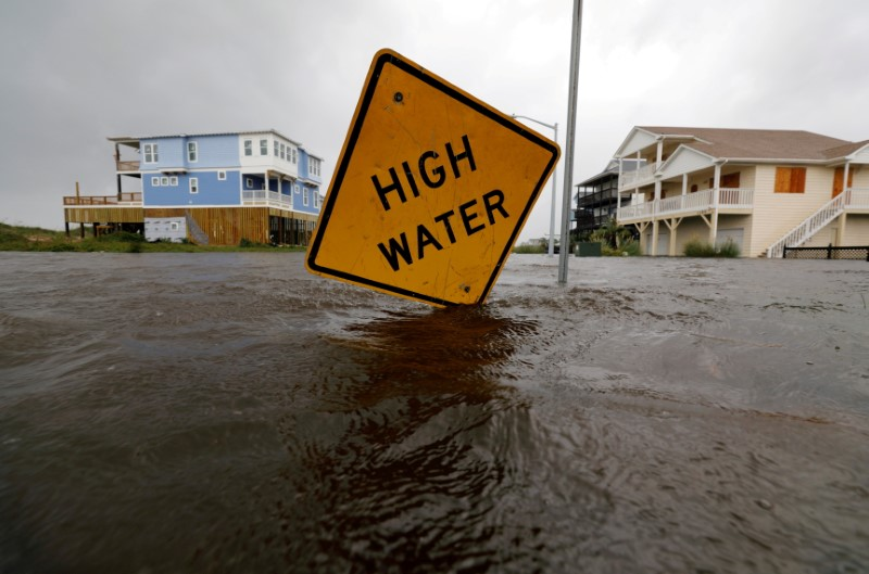 Flood waters lap at a high water warning sign that was partially pushed over by Hurricane Florence on Oak Island, North Carolina, U.S., September 15, 2018. REUTERS/Jonathan Drake/File Photo