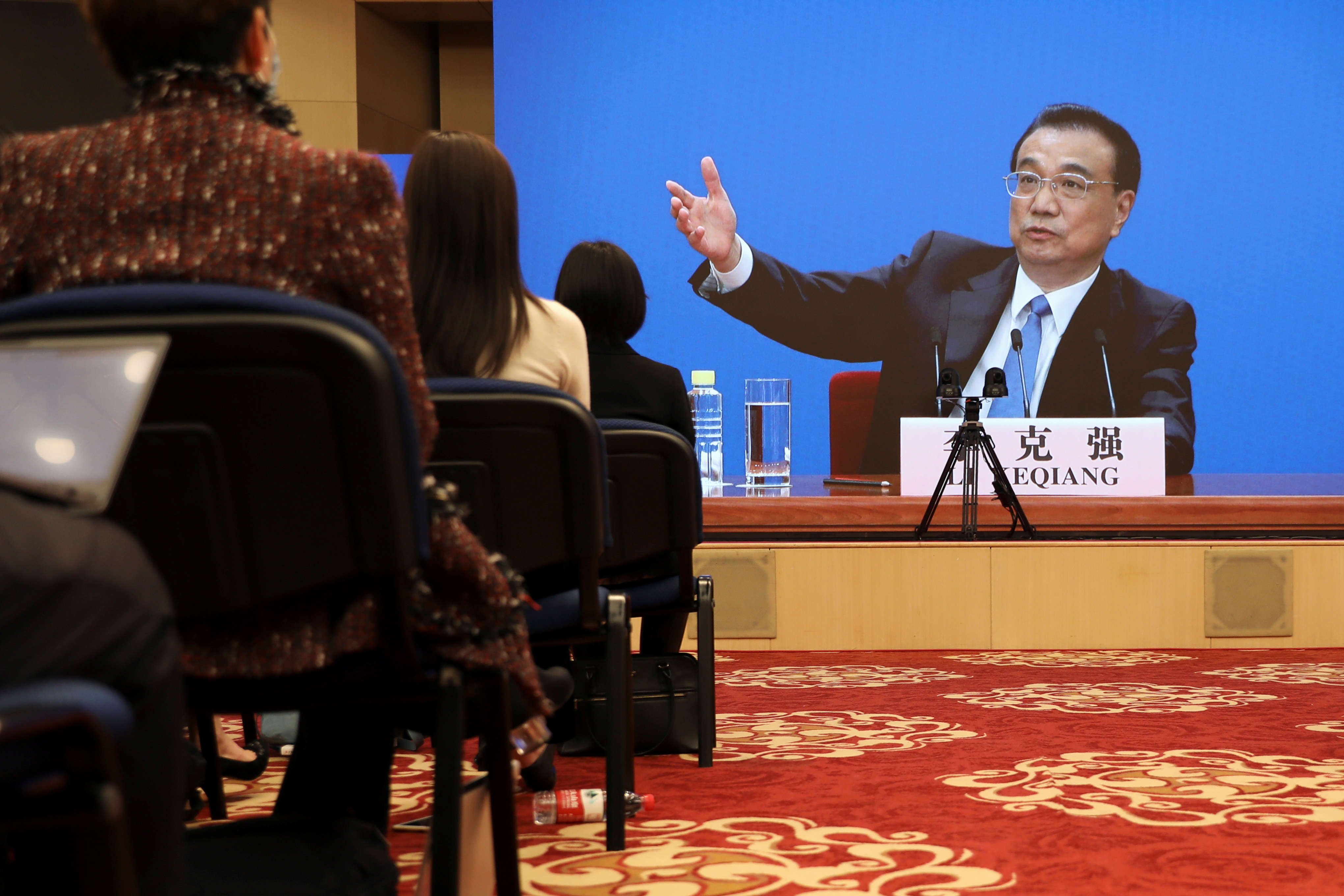 Chinese Premier Li Keqiang is seen on a screen during a news conference held via video link, following the closing session of the National People's Congress (NPC) in Beijing, China March 11, 2021. REUTERS/Martin Pollard