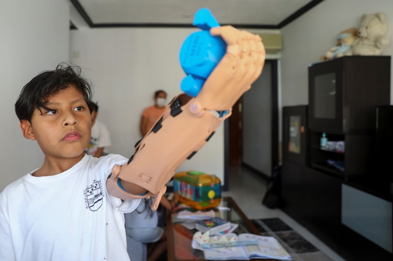 Juan Moyolema, an 8-year-old boy who was born missing the lower part of his left arm, raises a toy with a 3D printed tailor-made prosthetic given to him by Madrid-base social entity Ayudame3D at his home in Parla, near Madrid, Spain, May 18, 2021. Picture taken May 18, 2021. REUTERS/Sergio Perez