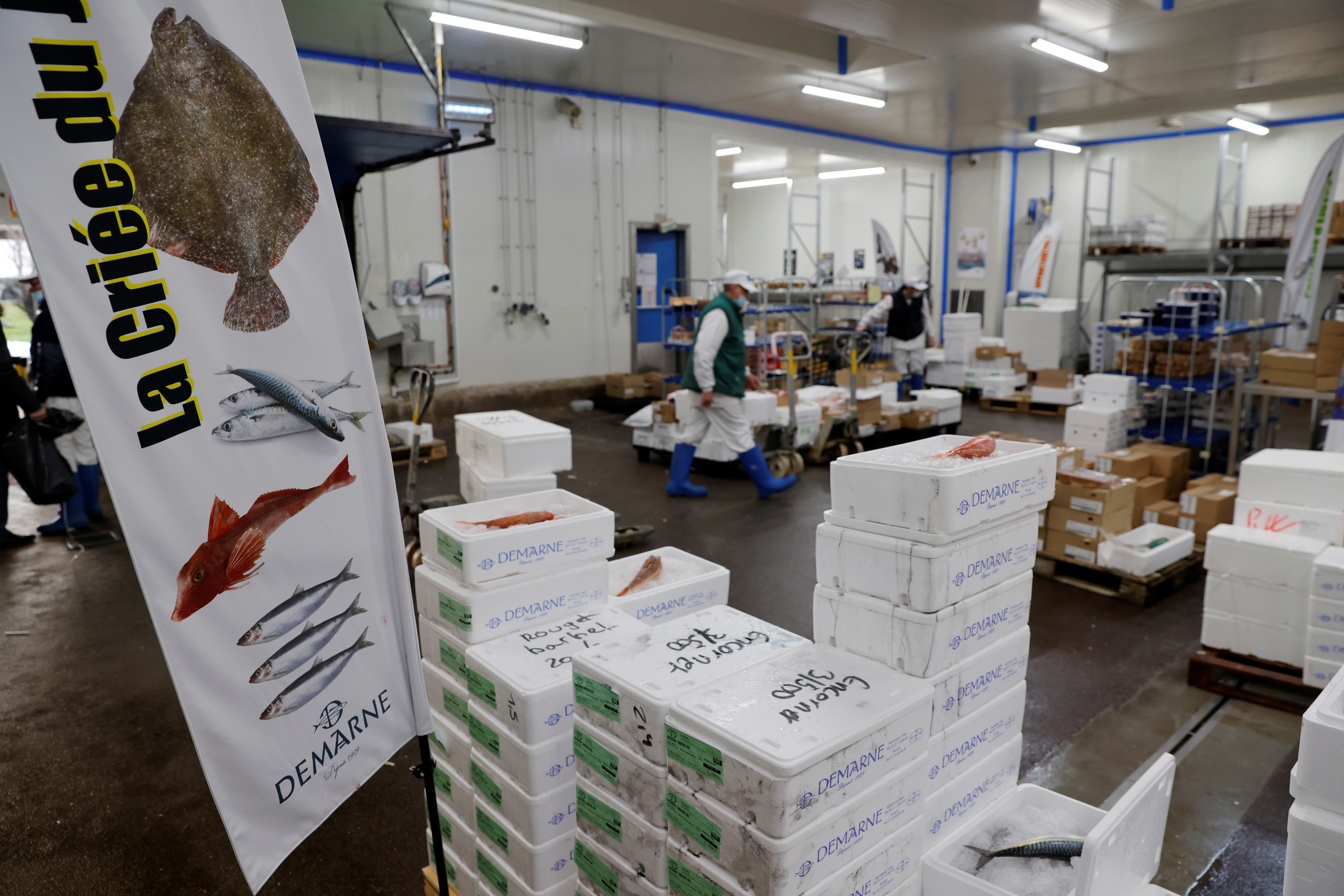 French workers move boxes in a fish processing plant in the port of Boulogne-sur-Mer, France, January 11, 2021. REUTERS/Pascal Rossignol