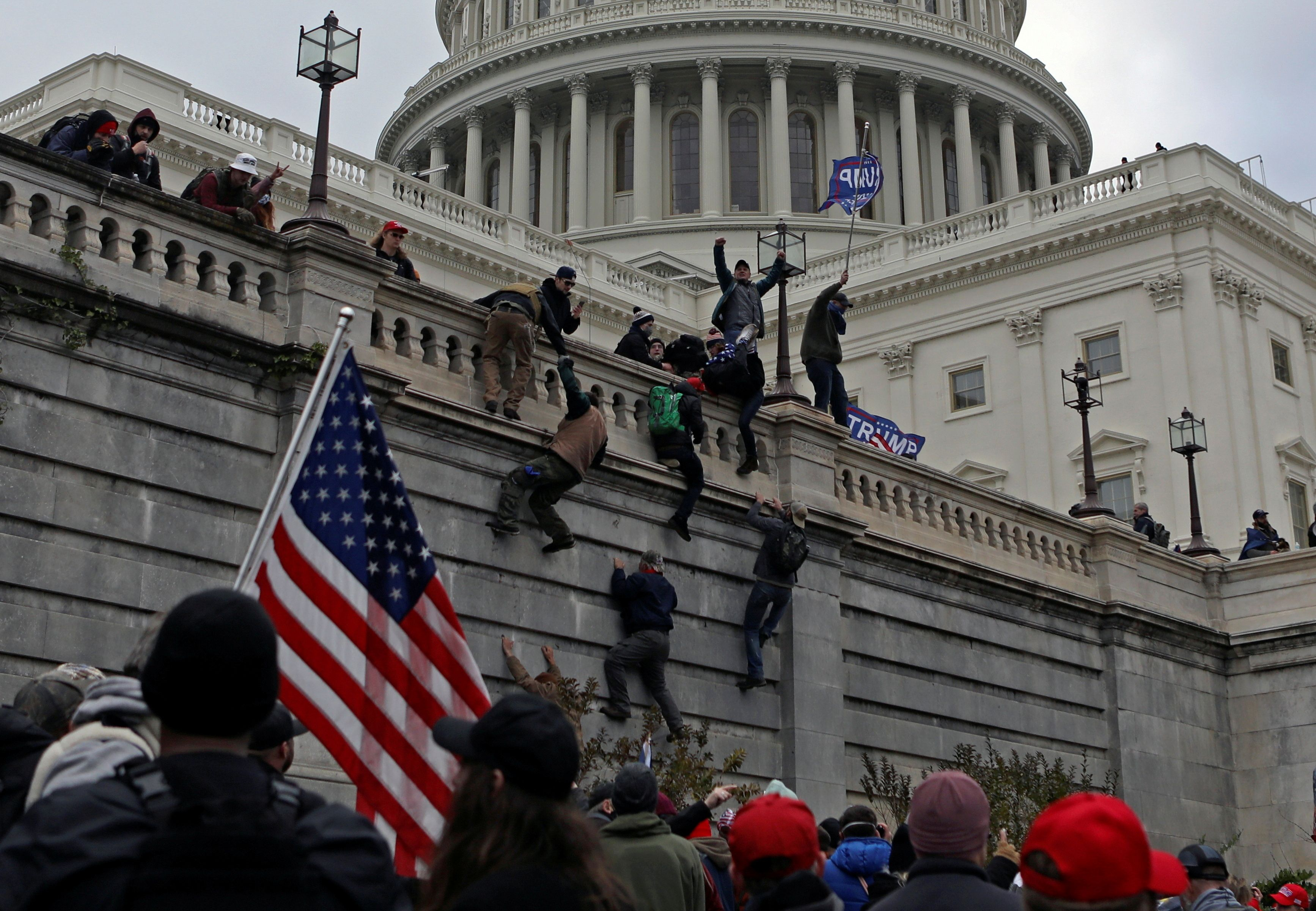 Supporters of U.S. President Donald Trump climb a wall during a protest against the certification of the 2020 presidential election results by the Congress, at the Capitol in Washington, U.S., January 6, 2021. Picture taken January 6, 2021. REUTERS/Jim Urquhart/File Photo