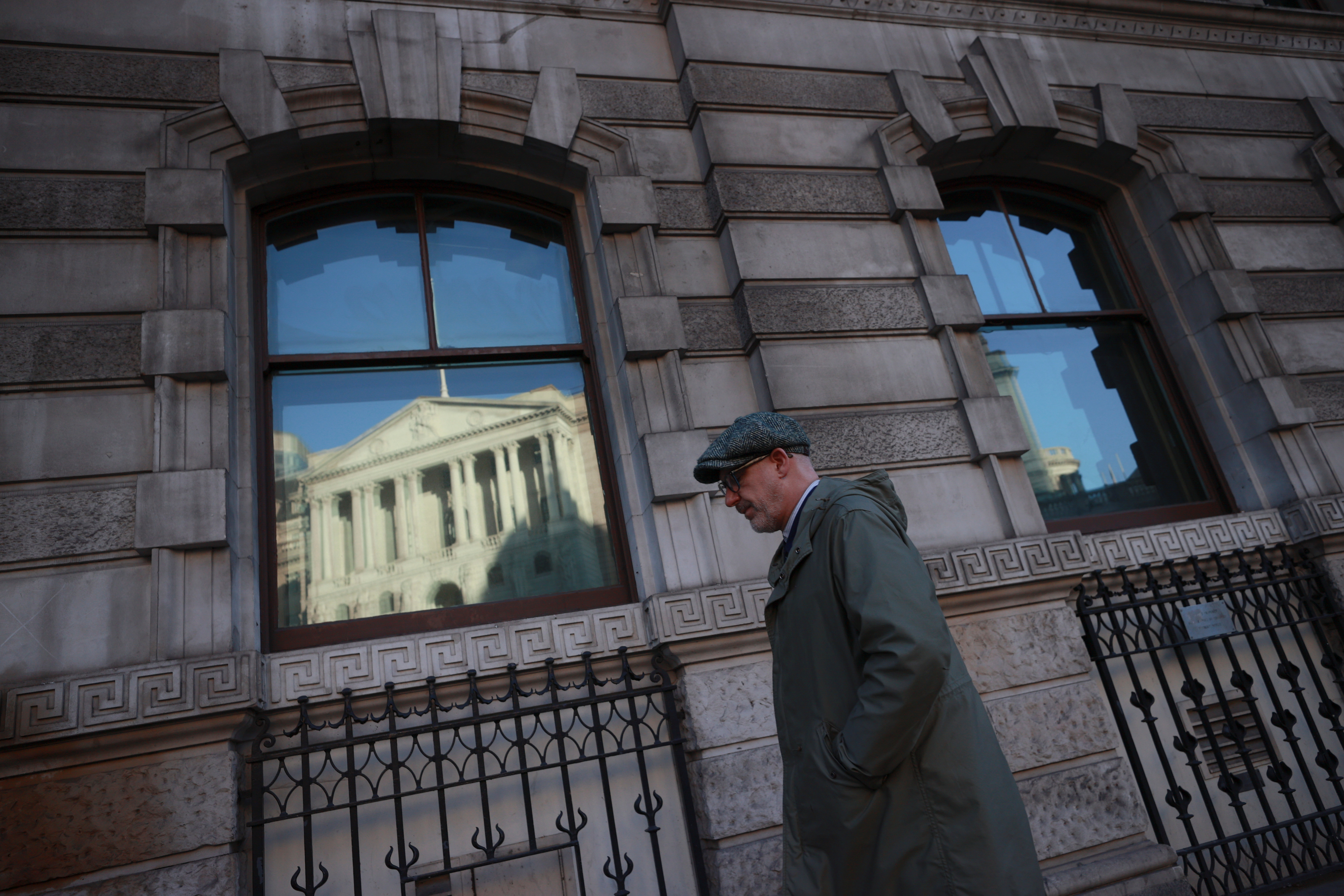 A man walks past a window reflecting the Bank of England, in London, Britain, December 17, 2020. REUTERS/Hannah McKay