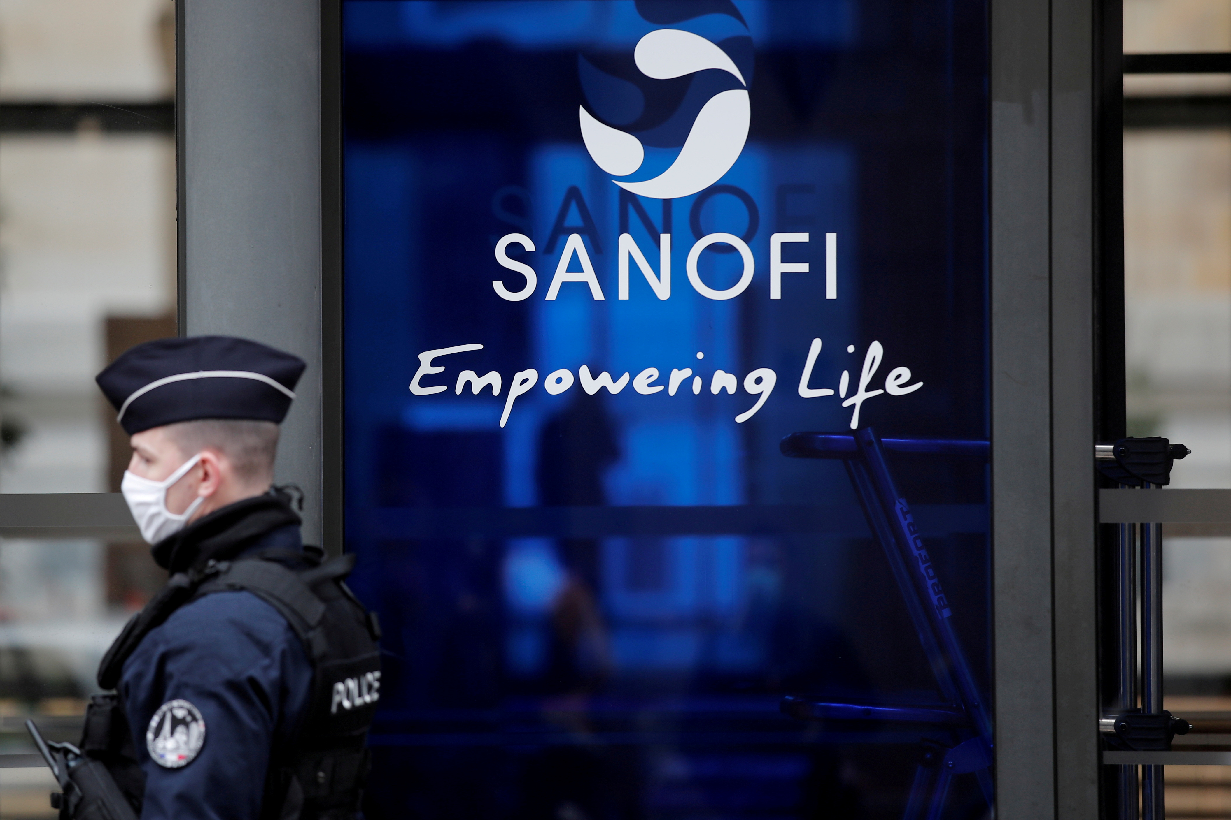 A French policeman stands in front of the Sanofi headquarters during a protest by Sanofi's workers against job cuts in Paris as part of a national day of strikes and protests against layoffs and government's economic and social policies amid the coronavirus disease (COVID-19) outbreak in France, France, February 4, 2021.  REUTERS/Benoit Tessier/File Photo