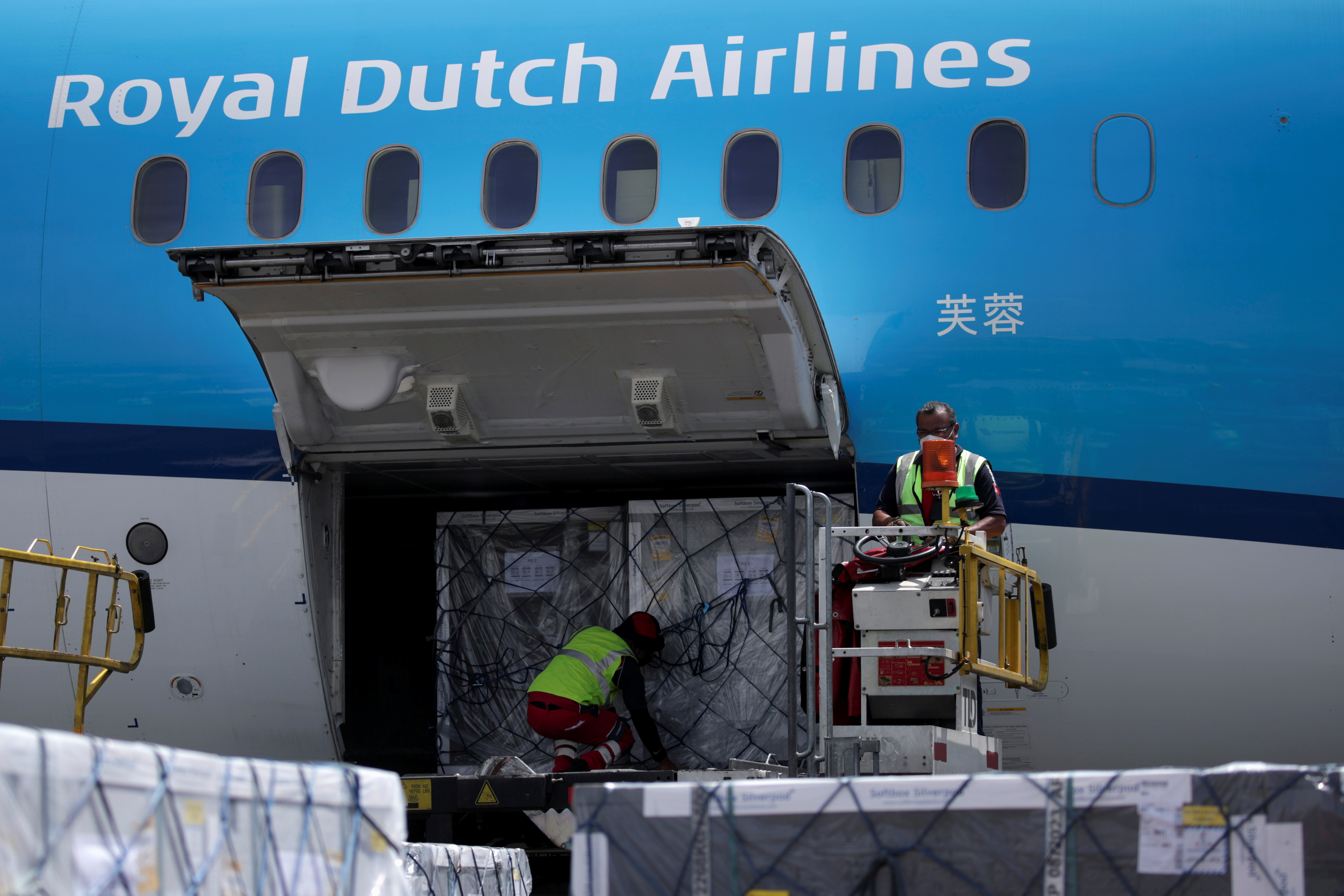 Workers unload a batch of AstraZeneca coronavirus disease (COVID-19) vaccines, delivered under the COVAX scheme, from a KLM Boeing 787 at Benito Juarez International Airport in Mexico City, Mexico May 27, 2021. REUTERS/Henny Romero/File Photo