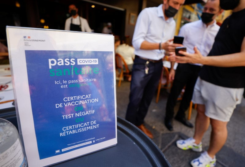 A man shows his COVID-19 health pass at a restaurant as France brings on tougher restrictions where a proof of immunity will now be required to access most public spaces and to travel by inter-city train, in Nice, France, August 9, 2021. REUTERS/Eric Gaillard