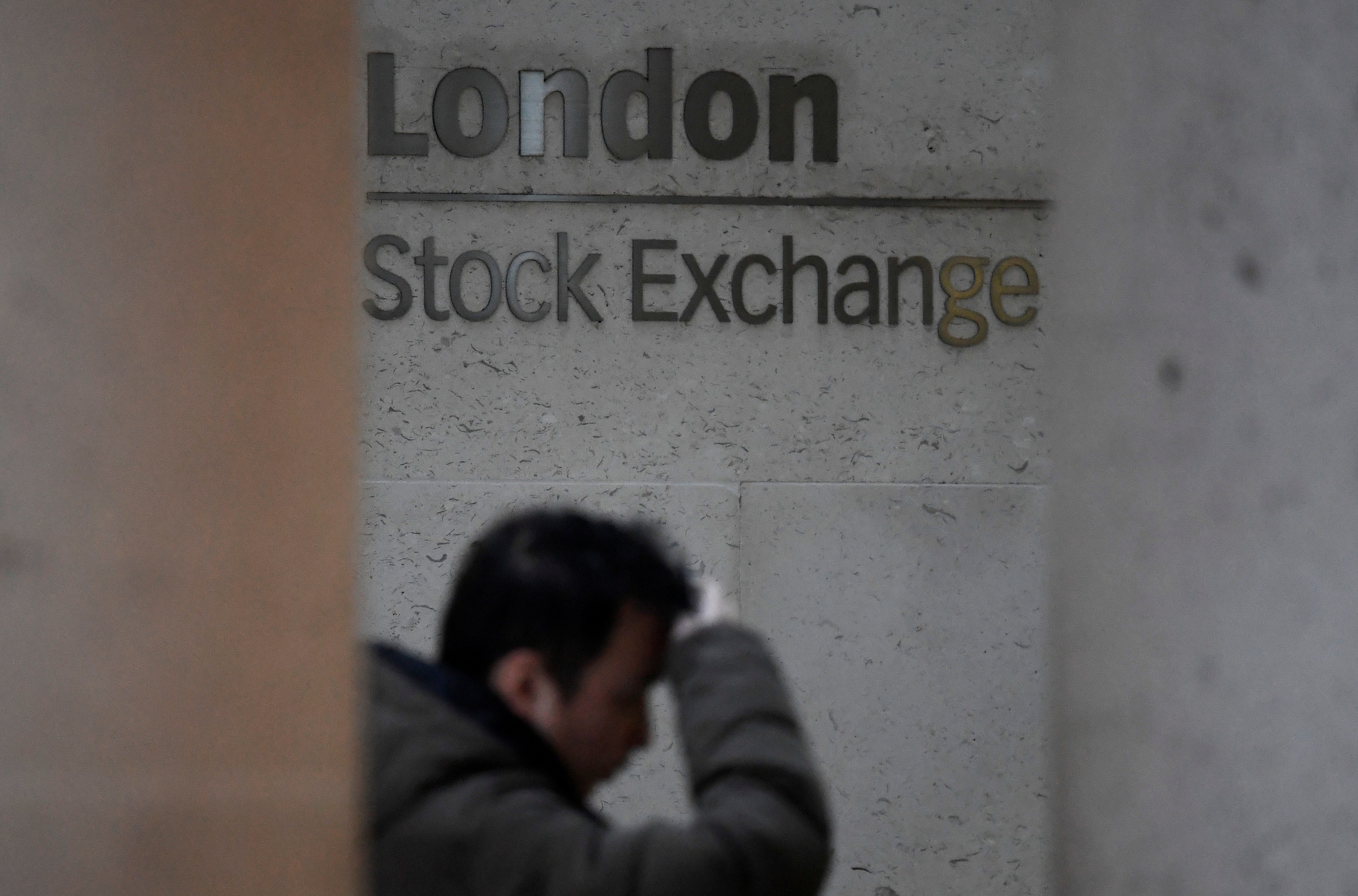 People walk past the London Stock Exchange Group offices in the City of London, Britain, December 29, 2017. REUTERS/Toby Melville