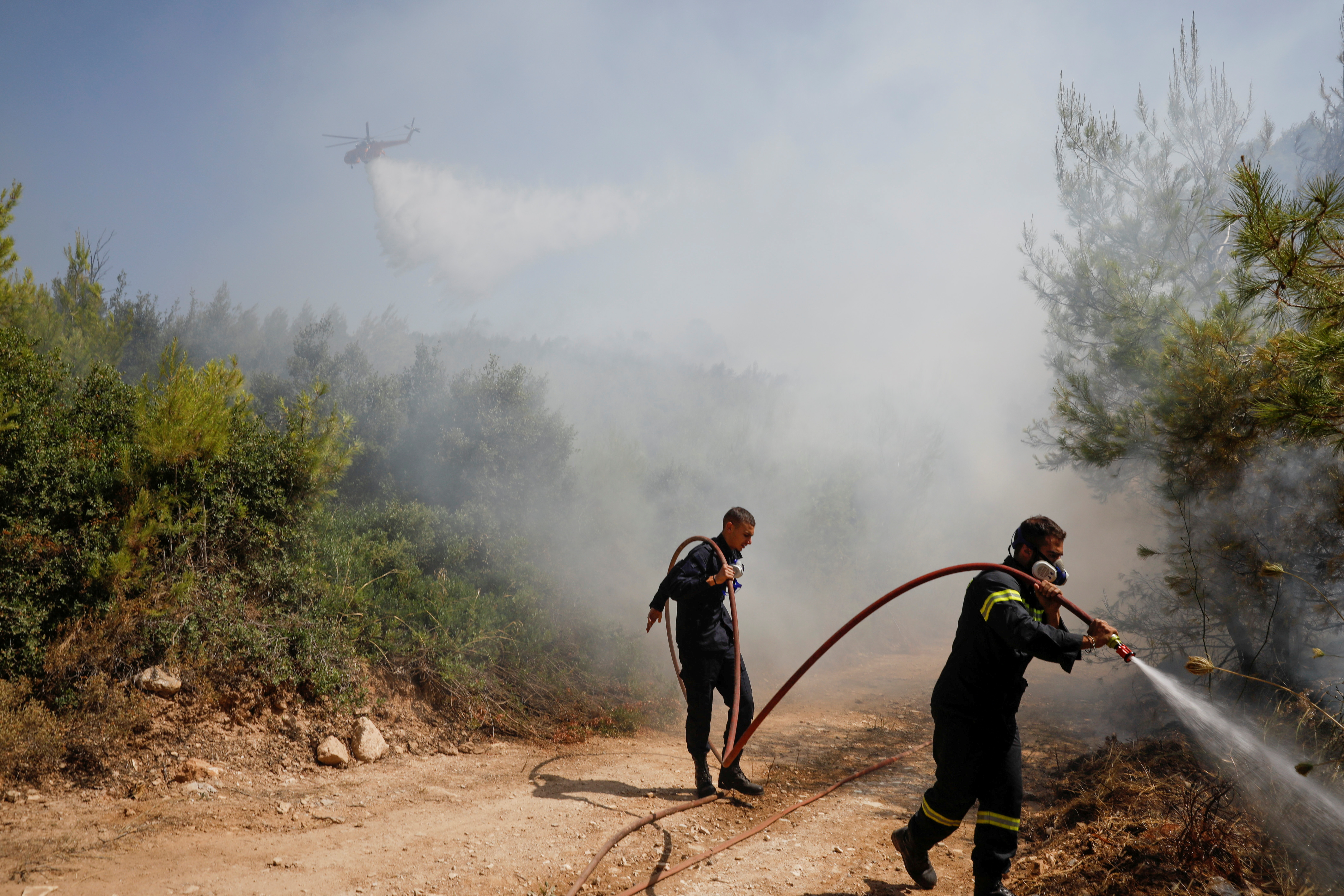 Firefighters spray water to extinguish a wildfire near the village of Rodopoli, north of Athens, Greece, July 27, 2021. REUTERS/Costas Baltas/File Photo