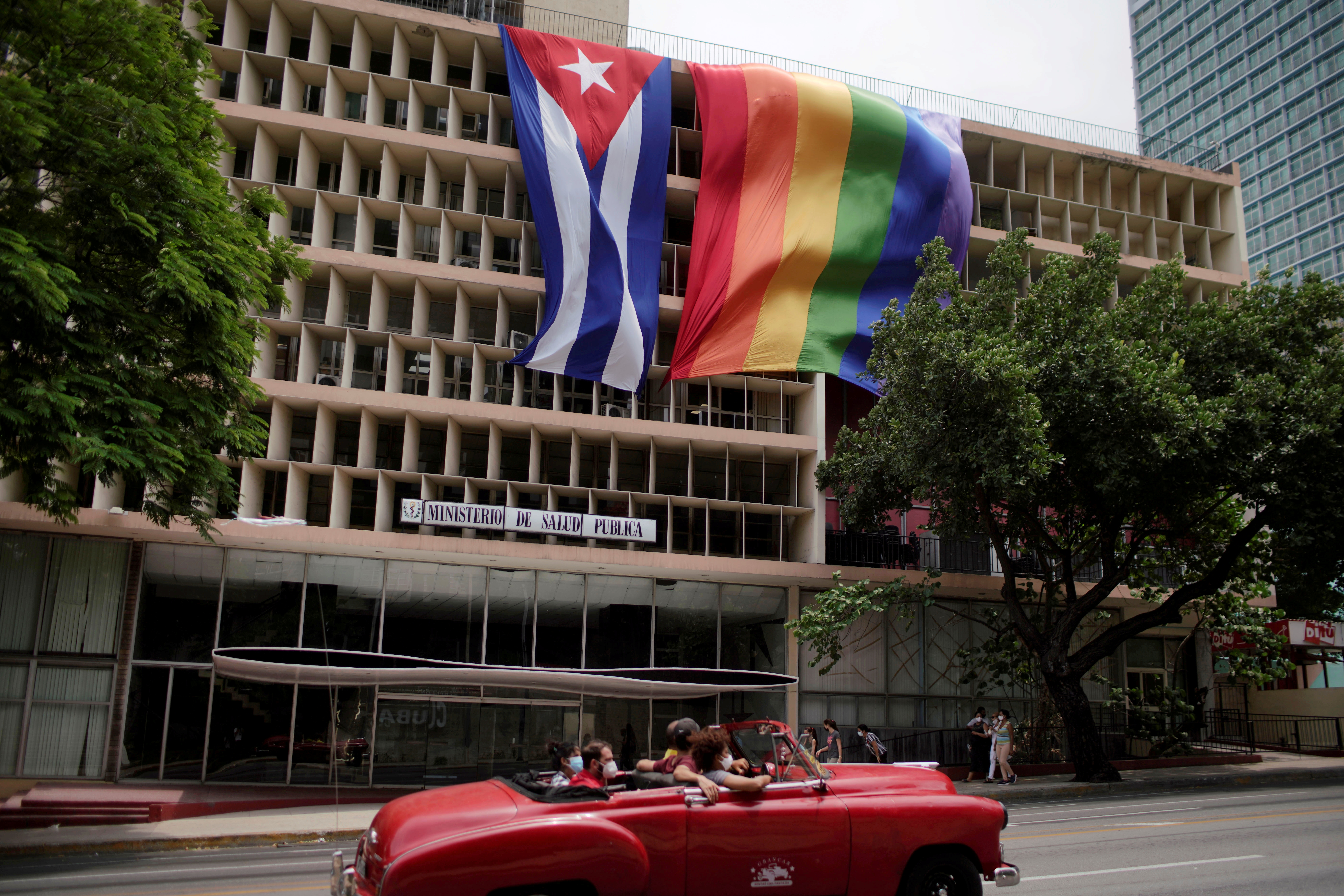 People pass in a vintage car in front of a rainbow flag hanging beside a Cuban flag at the Health Ministry building in Havana, Cuba, May 17, 2021. REUTERS/Alexandre Meneghini