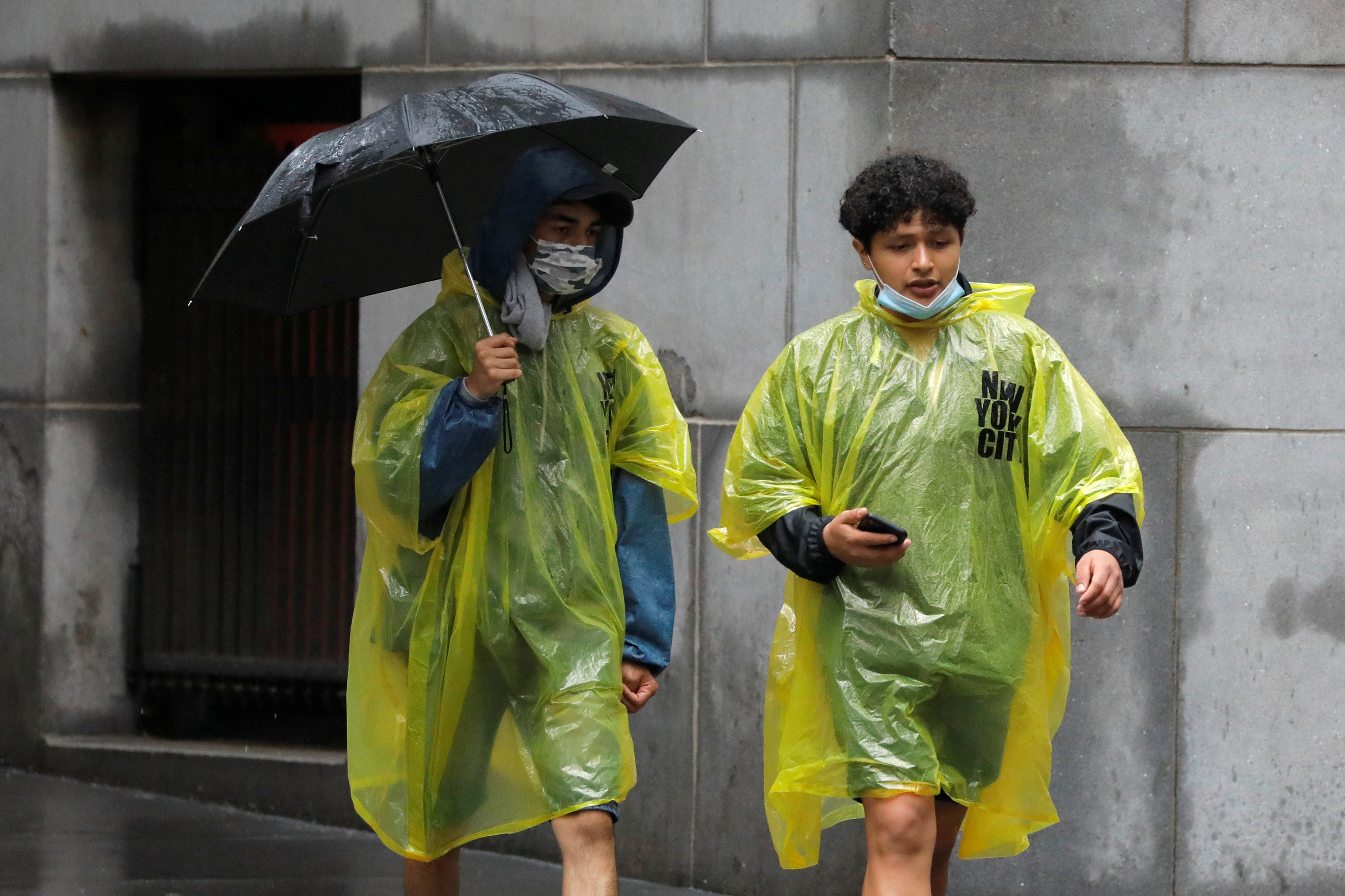 People in plastic rain ponchos walk through the Financial District as Tropical Storm Henri affected the area in Manhattan, New York City, U.S., August 23, 2021. REUTERS/Andrew Kelly