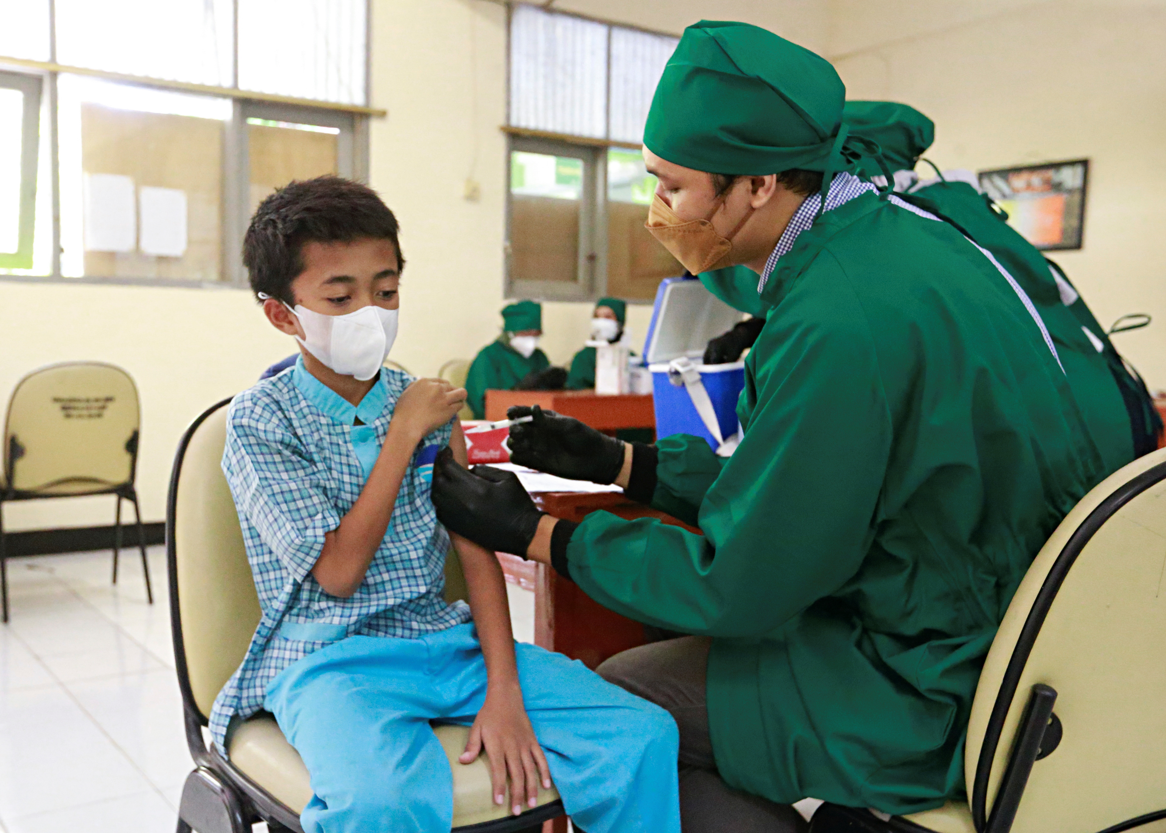 Zaidan Hadi, 12, receives a dose of the vaccine against the coronavirus disease (COVID-19) during a mass vaccination program for students at a school in Jakarta, Indonesia, July 15, 2021. REUTERS/Ajeng Dinar Ulfiana
