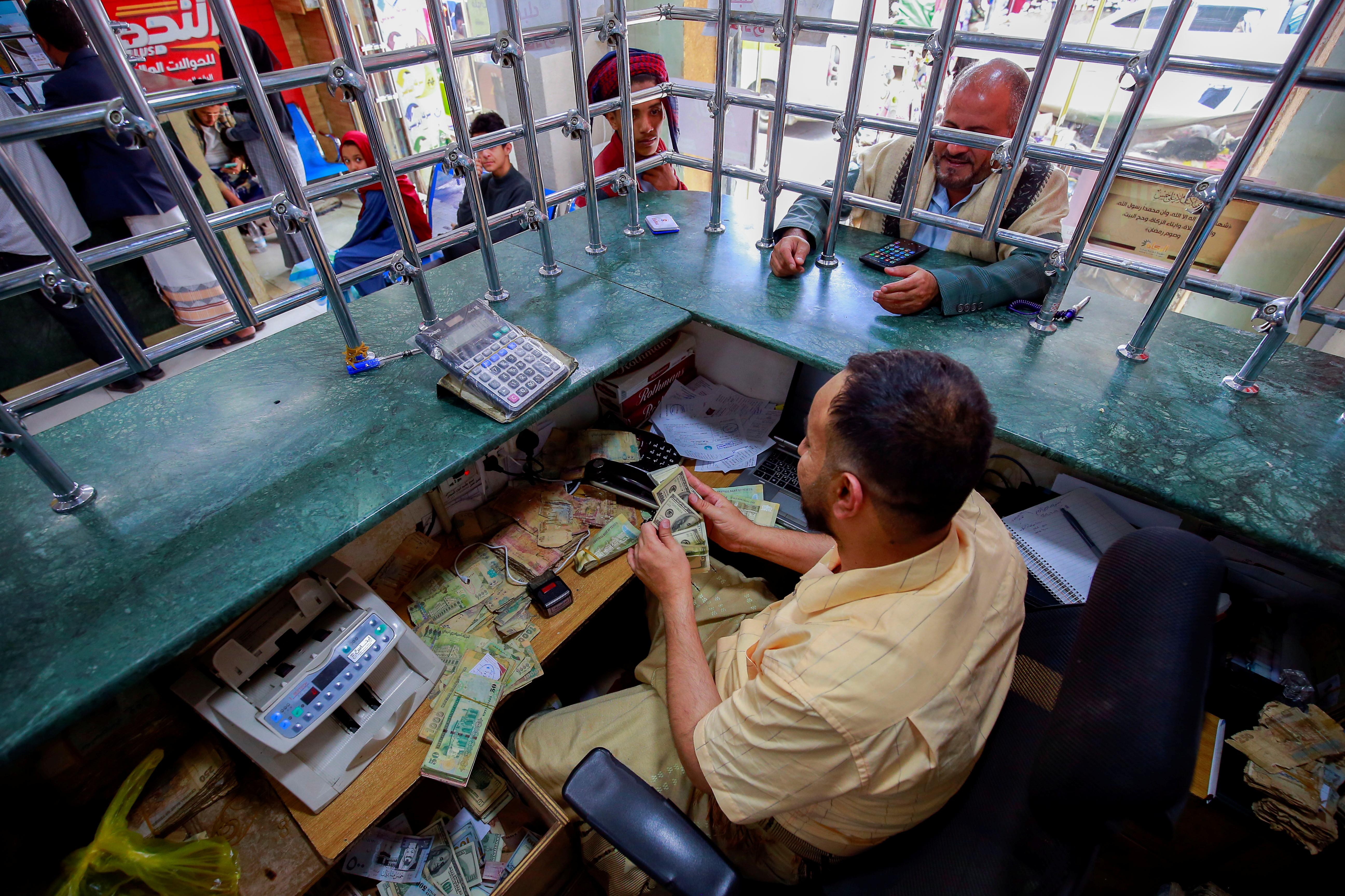 A currency exchange worker sits behind security bars at an exchange company in Sanaa, Yemen June 28, 2021. REUTERS/Nusaibah Almuaalemi