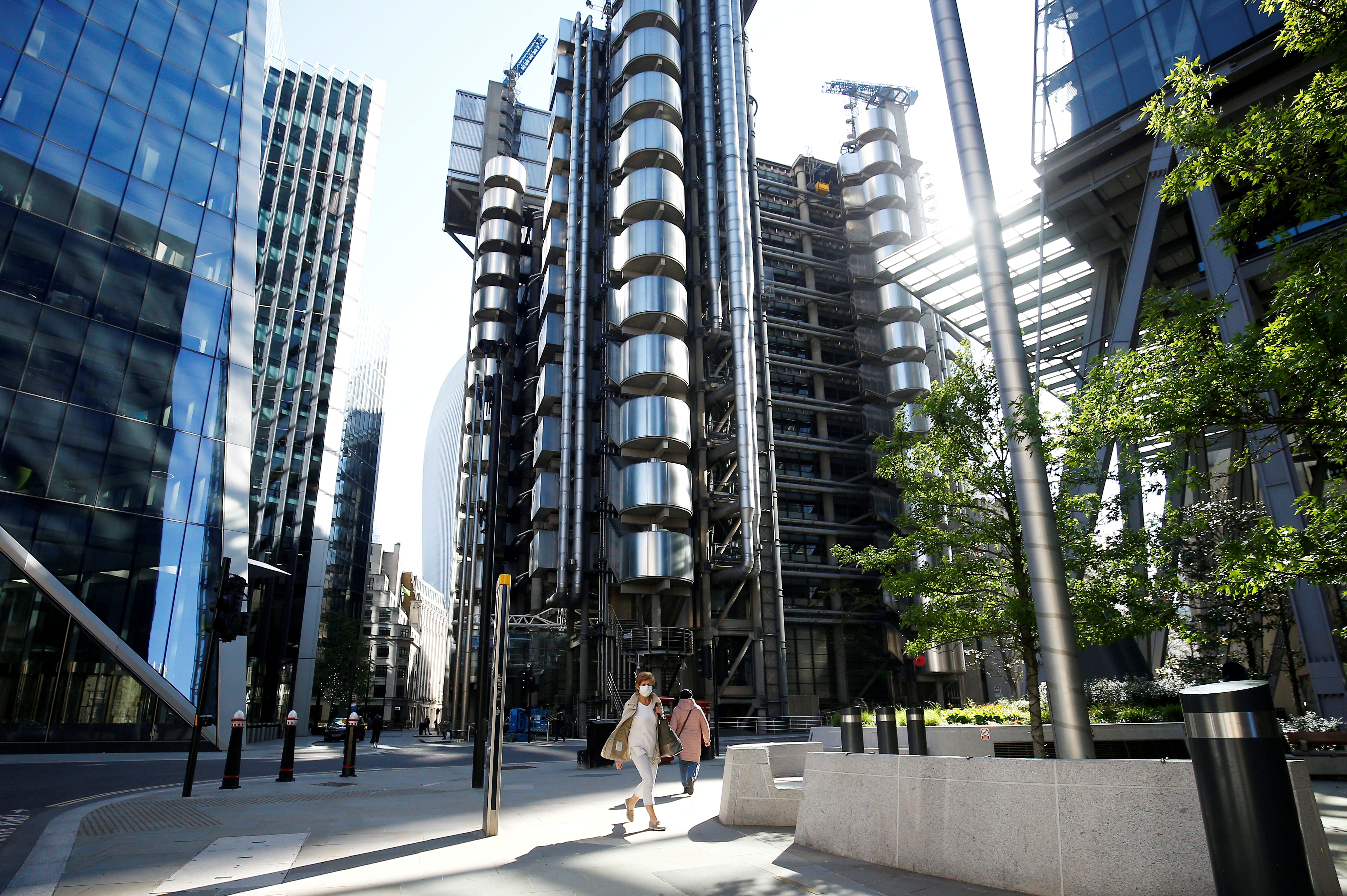 A woman wearing a face mask walks past the Lloyd's of London building following the outbreak of the coronavirus disease (COVID-19), London, Britain, May 6, 2020. REUTERS/Henry Nicholls/File Photo
