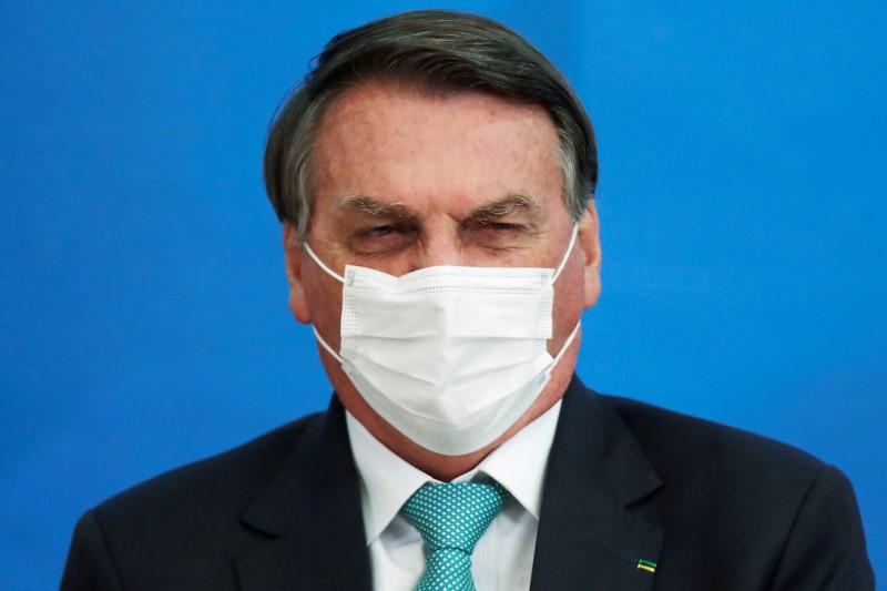 Brazil's President Jair Bolsonaro reacts during a ceremony of signing the Vaccine Technology Transfer Agreement for Oxford/AstraZeneca coronavirus disease (COVID-19) vaccines, in Brasilia, Brazil, June 1, 2021. REUTERS/Ueslei Marcelino