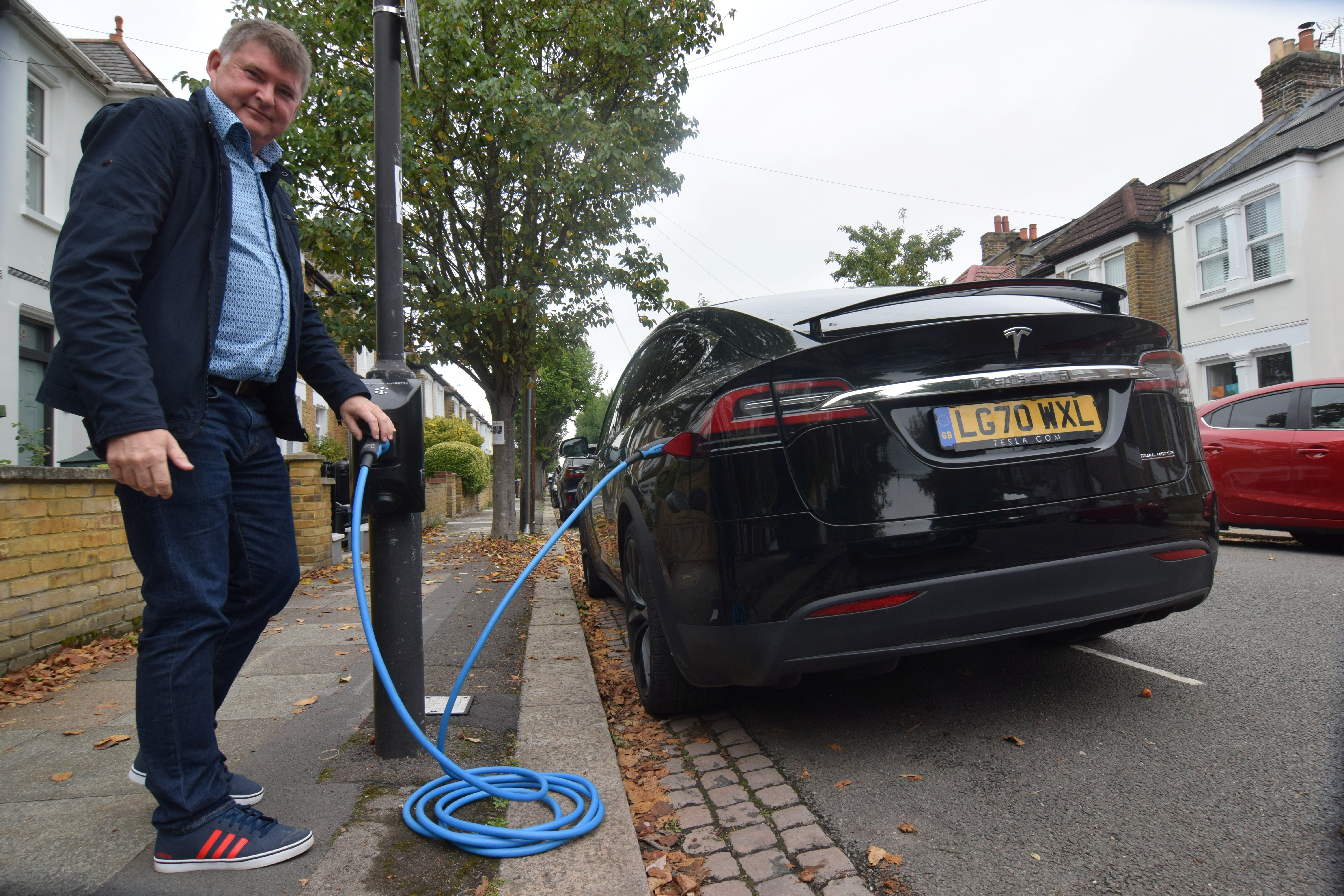 Richard Stobart, CEO of an electric vehicle charging system startup company Char.gy, demonstrates one of the company's lamp post chargers in London, Britain, September 20, 2021. REUTERS/Nick Carey