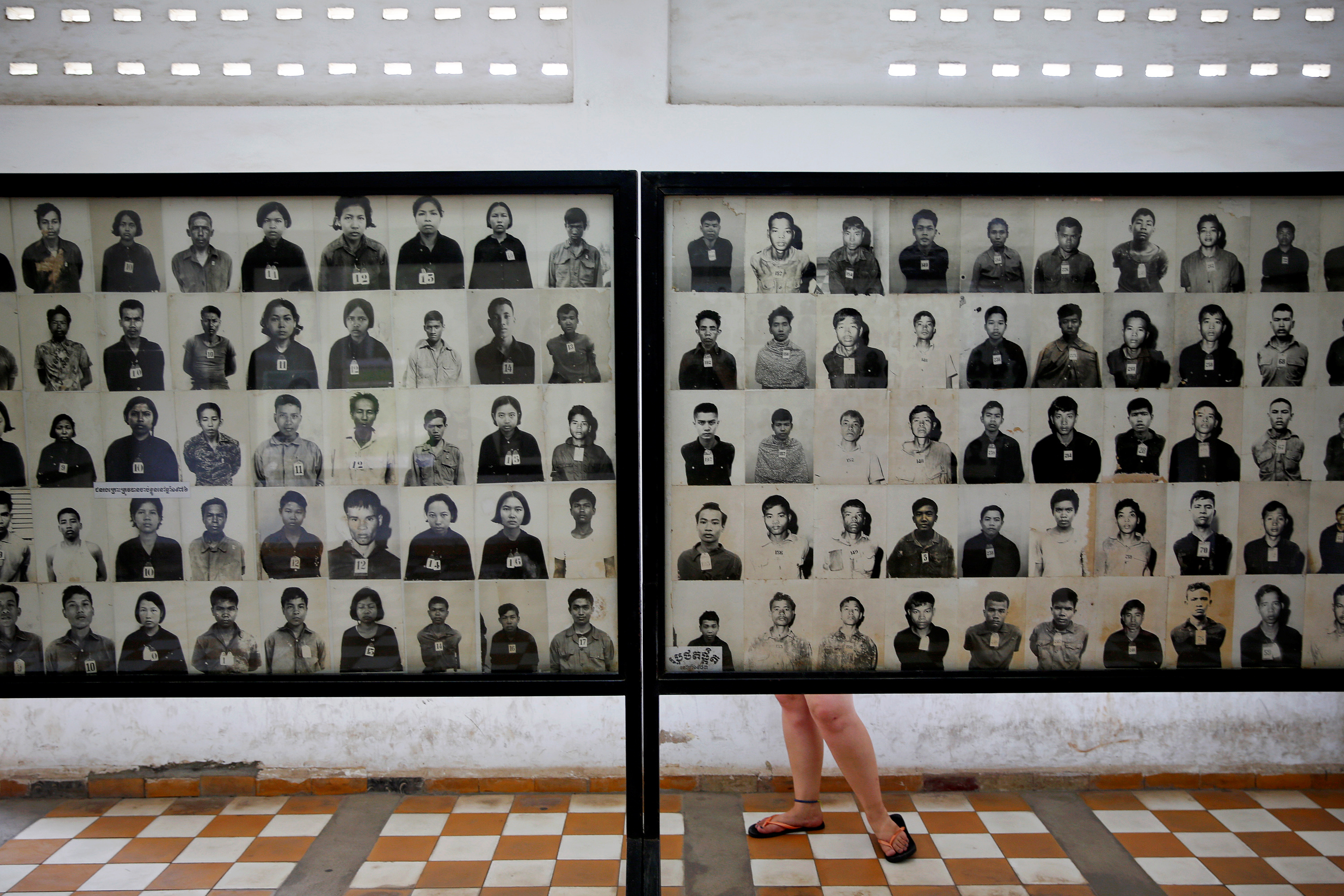 A visitor looks at pictures of victims of Khmer Rouge regime at the former notorious Tuol Sleng prison that is now the Genocide Museum, in Phnom Penh August 5, 2014. REUTERS/Damir Sagol