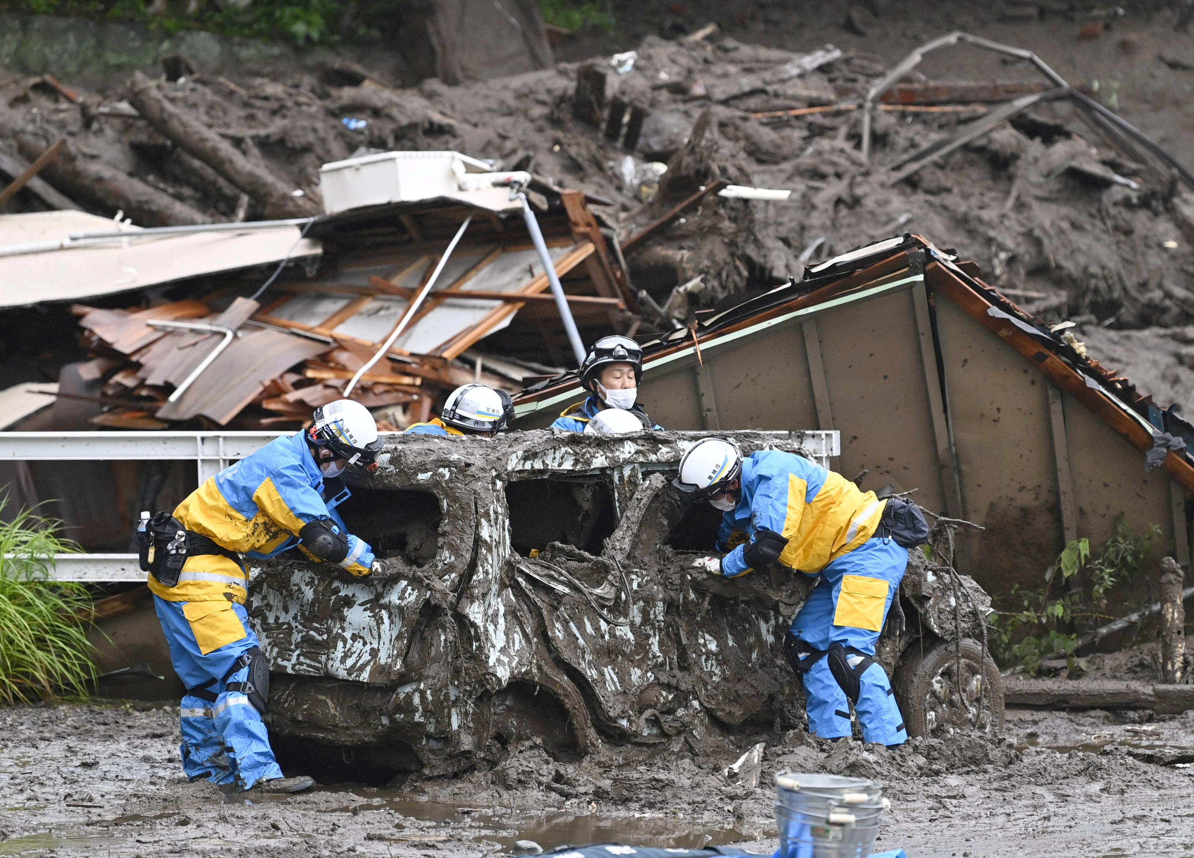 Police officers conduct search and rescue operation around a destroyed car at a mudslide site caused by heavy rain at Izusan district in Atami, west of Tokyo, Japan July 4, 2021, in this photo taken by Kyodo. Kyodo/via REUTERS
