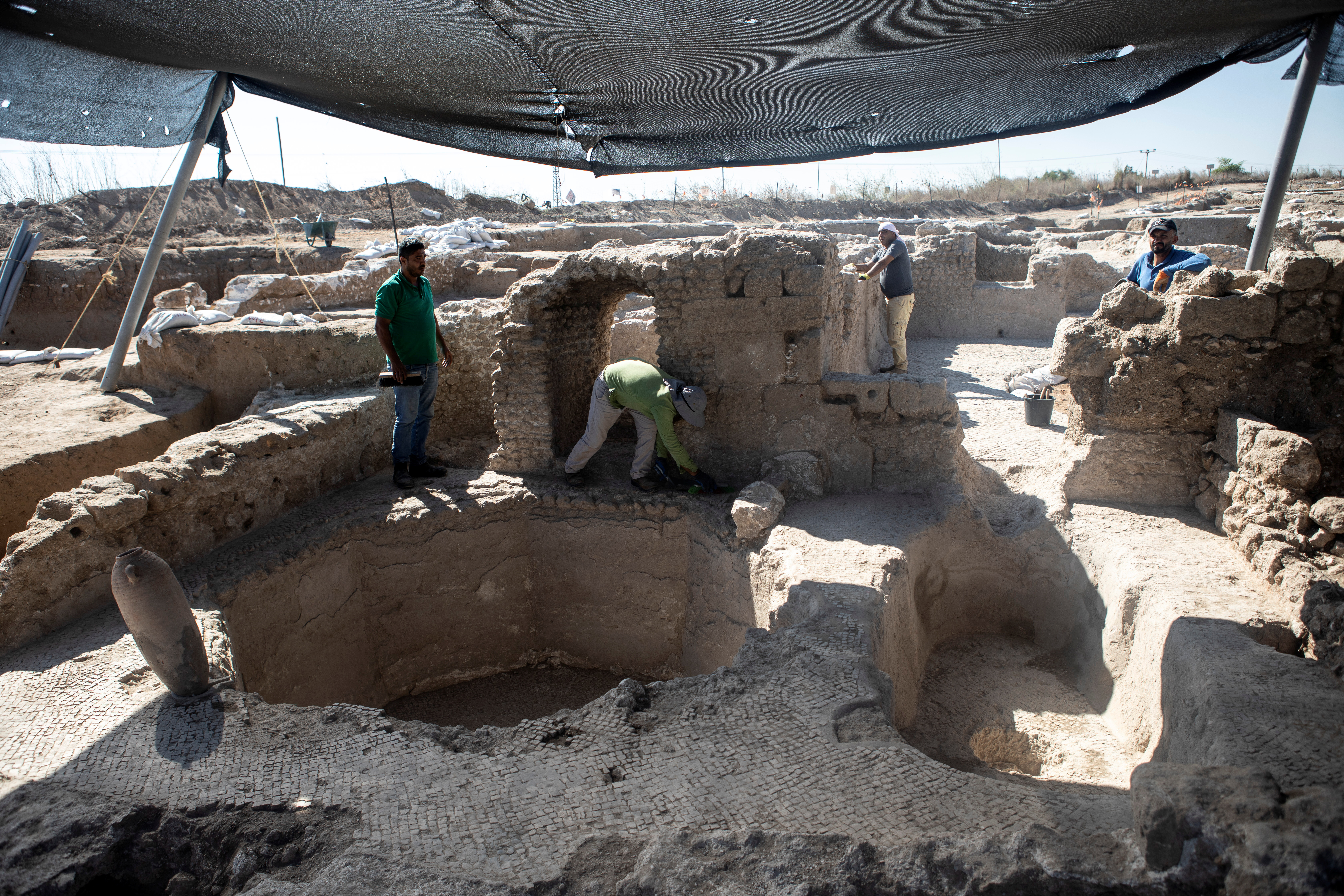 Israel Antiquities Authority workers stand at the remains of a 1500-year-old Byzantine winery in Yavne, Israel October 11, 2021. REUTERS/Nir Elias