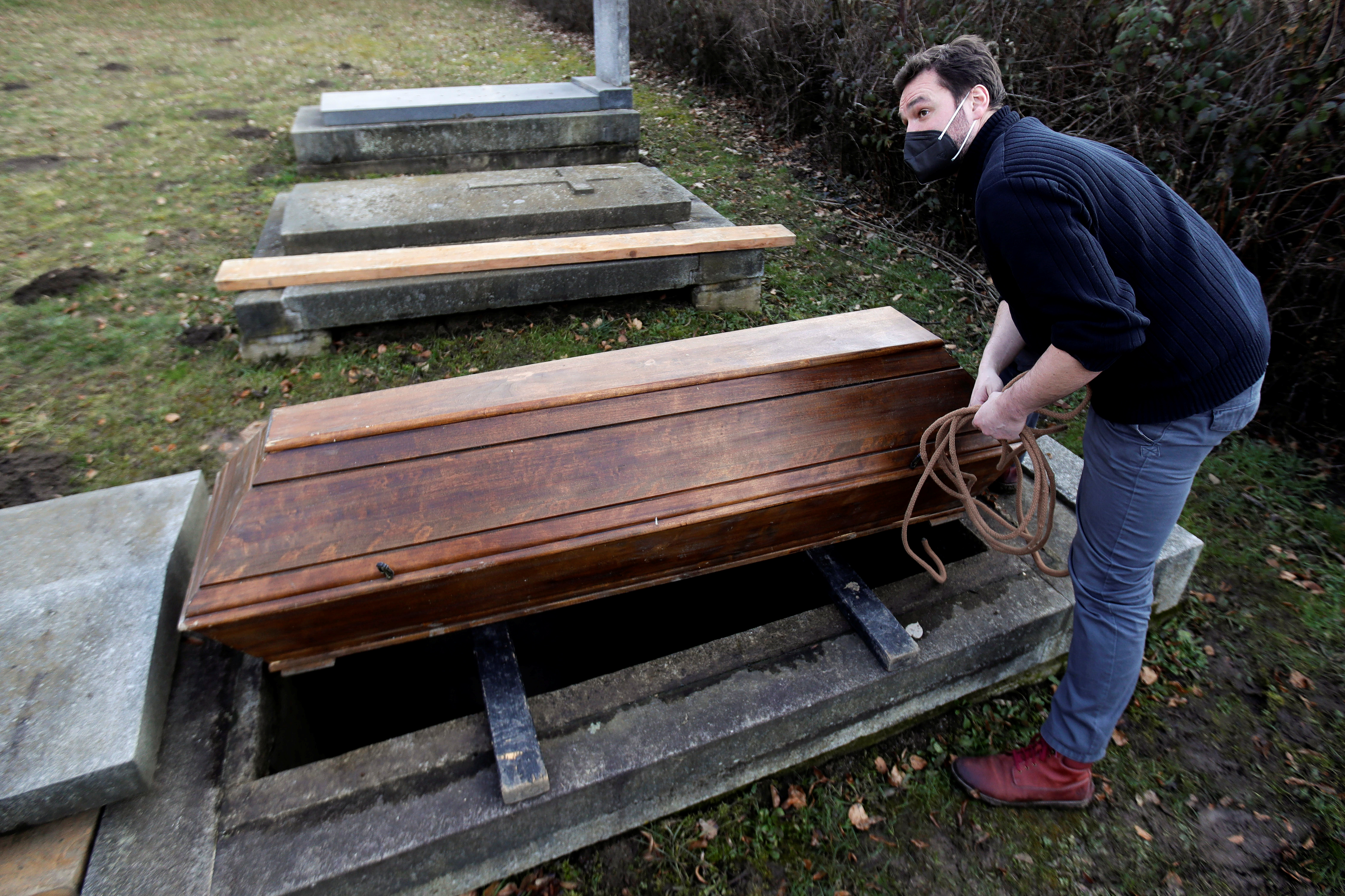An actor Tomas Novotny secures an empty coffin at a training cemetery as a part of his re-qualification procedure amid the coronavirus disease (COVID-19) outbreak in Prague, Czech Republic, March 9, 2021. Picture taken March 9, 2021.   REUTERS/David W Cerny