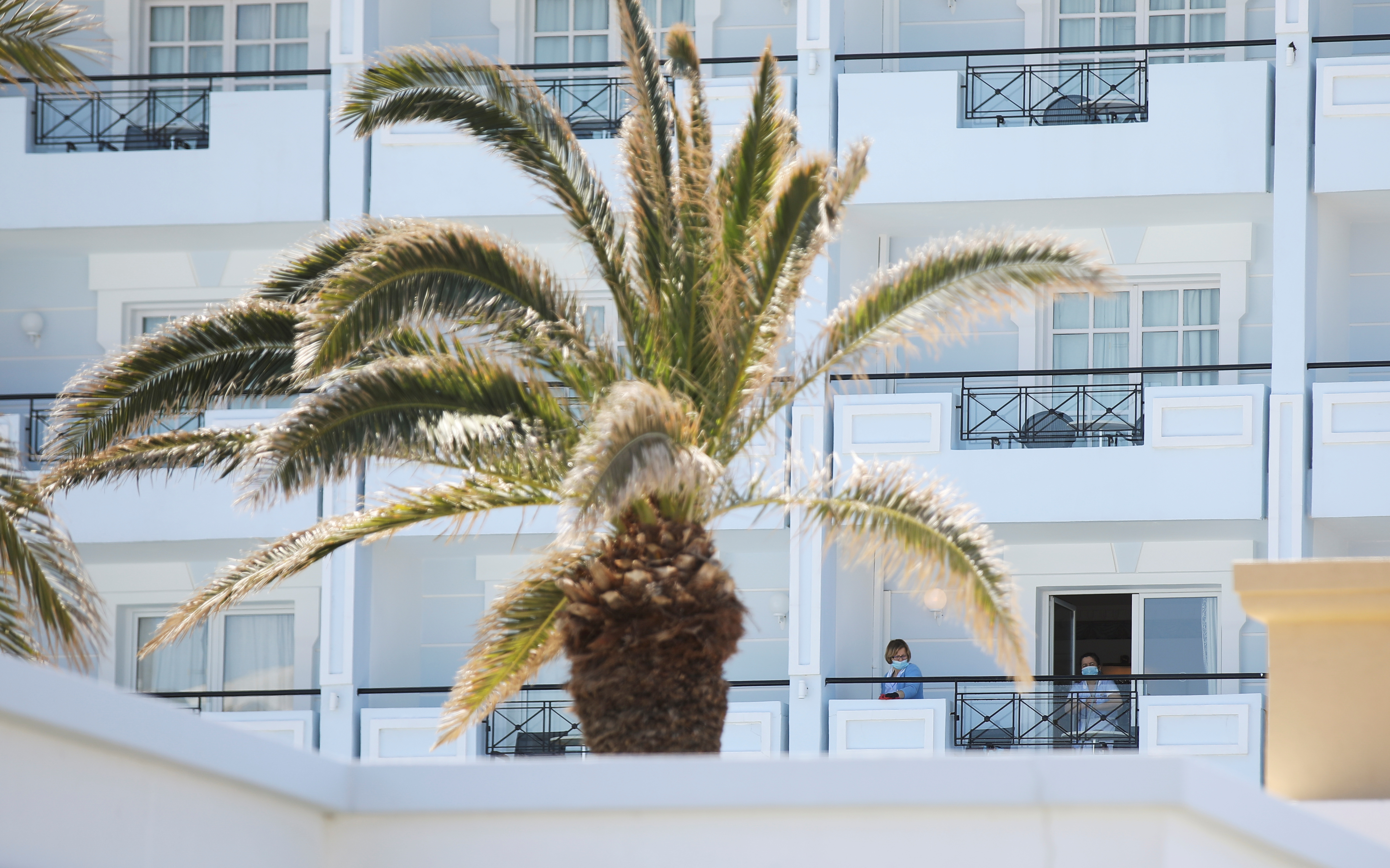 People are seen at a balcony of the Mitsis Grand Hotel Beach amid the coronavirus disease (COVID-19) outbreak in Rhodes on the island of Rhodes, Greece April 12, 2021. REUTERS/Louiza Vradi