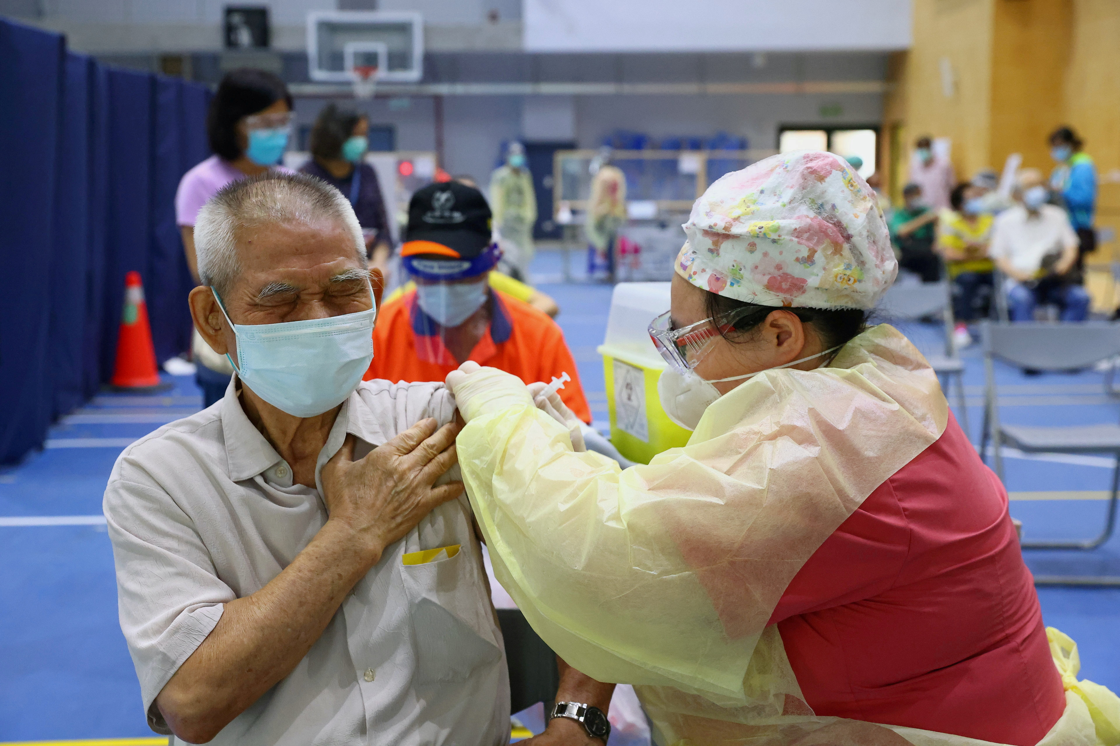 A medical worker administers a dose of the AstraZeneca vaccine against the coronavirus disease (COVID-19) to a man during a vaccination session for elderly people over 75 years old, at a stadium in New Taipei City, Taiwan June 25, 2021. REUTERS/Ann Wang/File Photo