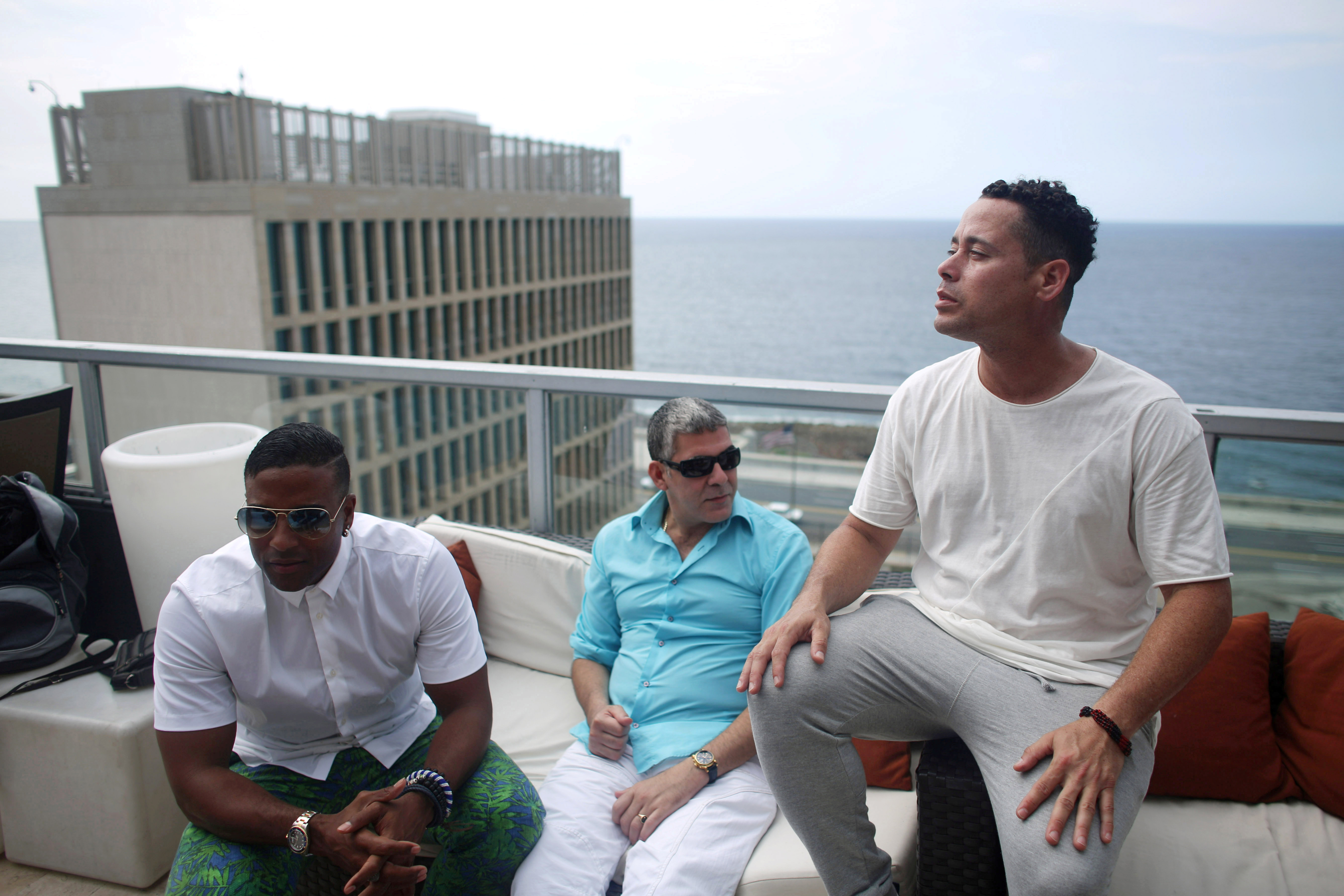 (L-R) Members of the Cuban fusion group Orishas - Yotuel, Roldan and Ruzzo - give an interview from the top of a building in Havana, Cuba, June 22, 2016. REUTERS/Alexandre Meneghini/File Photo