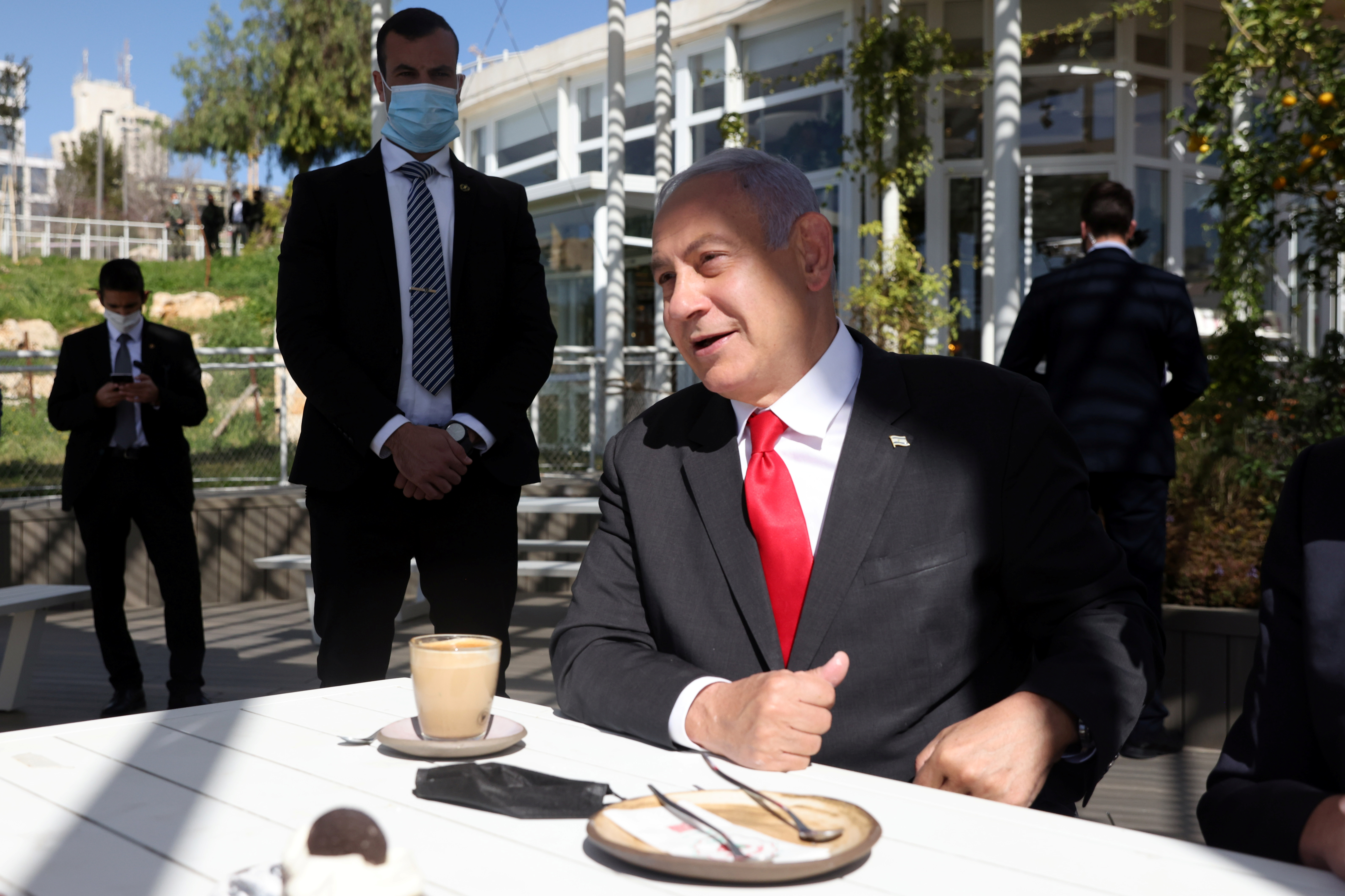 Israel Prime Minister, Benjamin Netanyahu gestures as he sits in a cafe while Israel further eases coronavirus disease (COVID-19) restrictions in Jerusalem March 7, 2021 REUTERS/ Ronen Zvulun