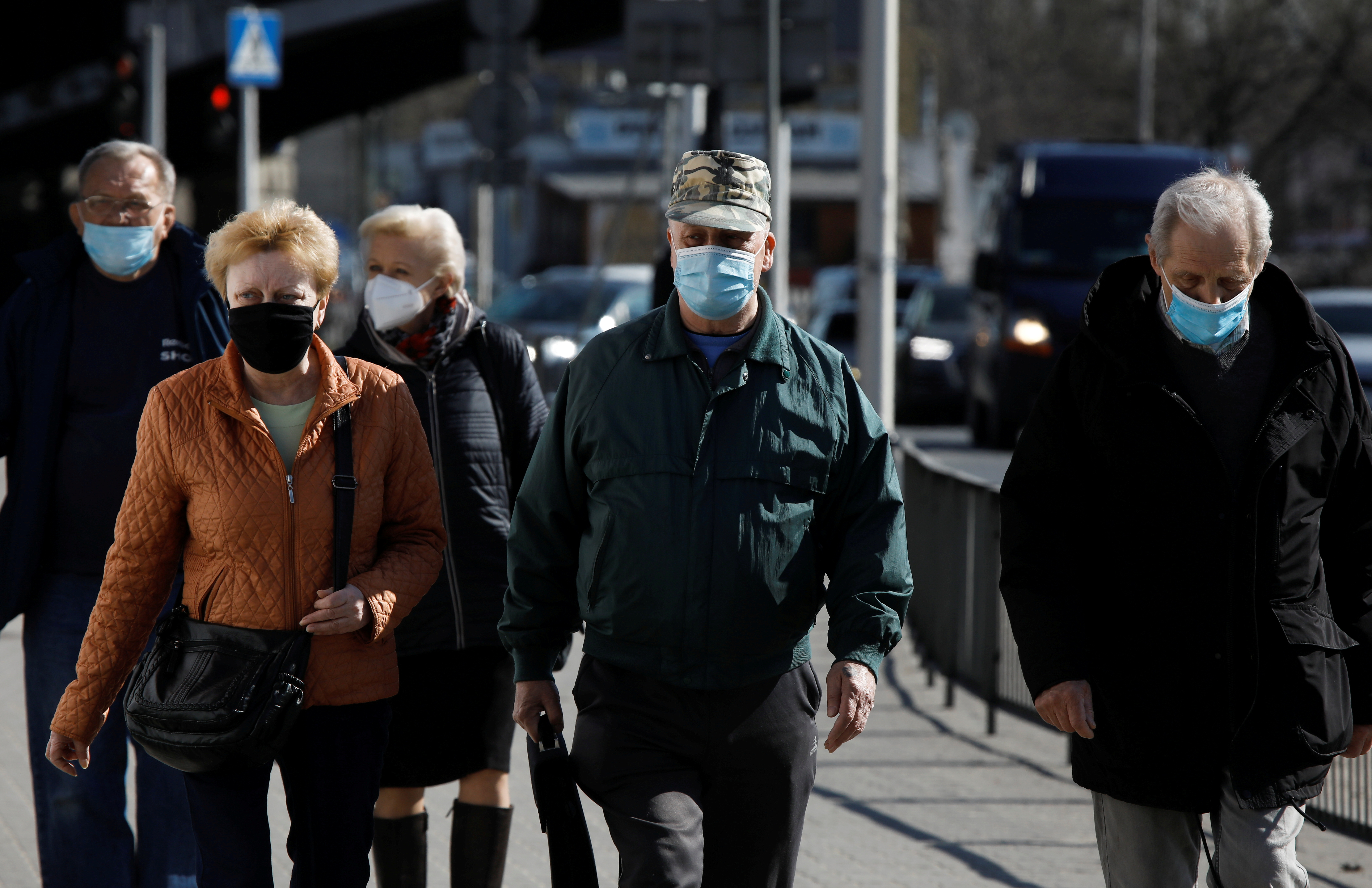 People wearing protective masks walk in Warsaw, Poland, April 2, 2021. REUTERS/Kacper Pempel/File Photo