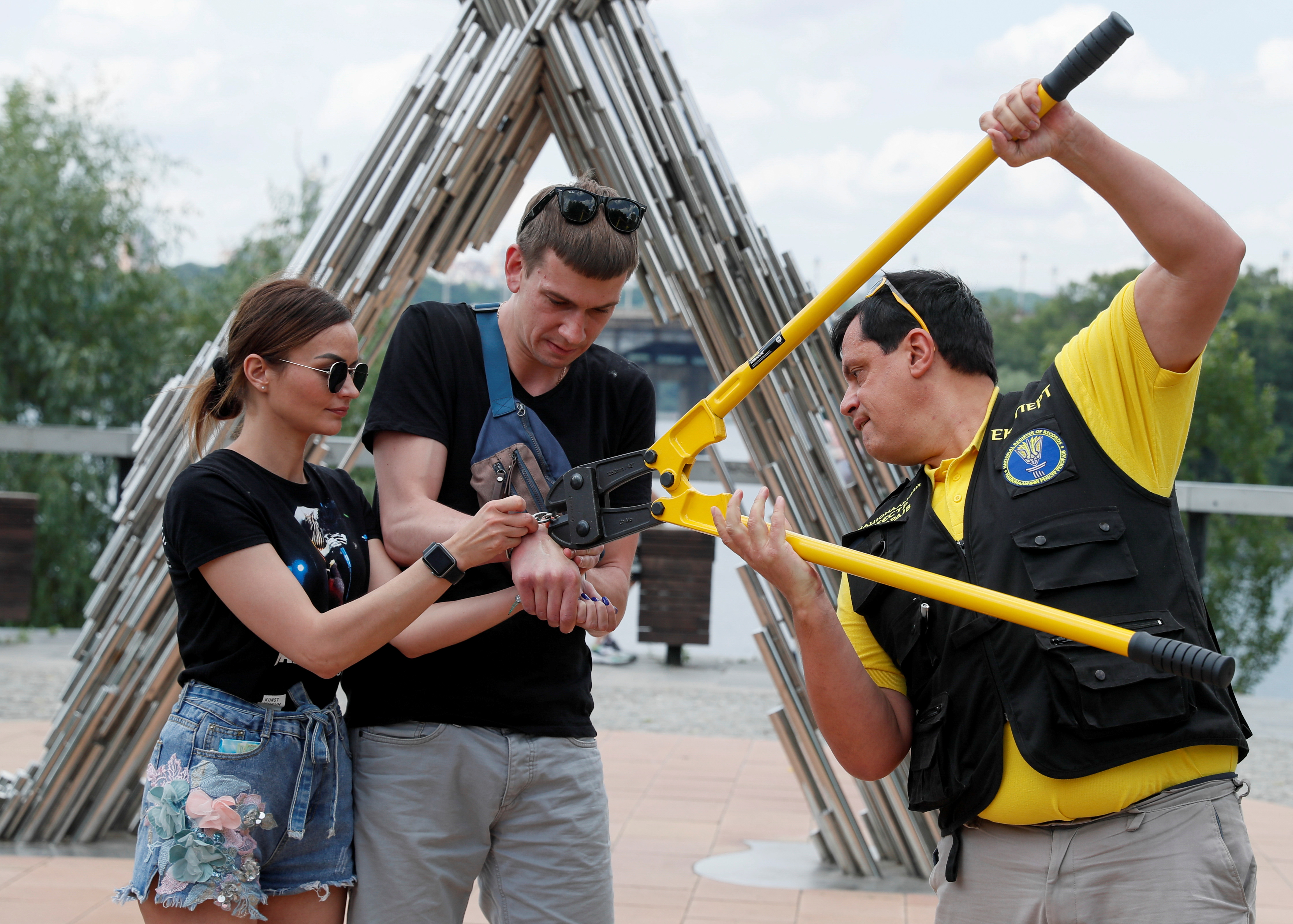 Alexandr Kudlay and Viktoria Pustovitova, who handcuffed themselves and spent 123 days together, have the chain dismantled by a representative from a Ukrainian record book in Kyiv, Ukraine June 17, 2021. The Ukrainian couple split up after 123 days handcuffed together, shedding their bonds on national TV and saying the experiment had brought home uncomfortable truths. Picture taken June 17, 2021. REUTERS/Gleb Garanich