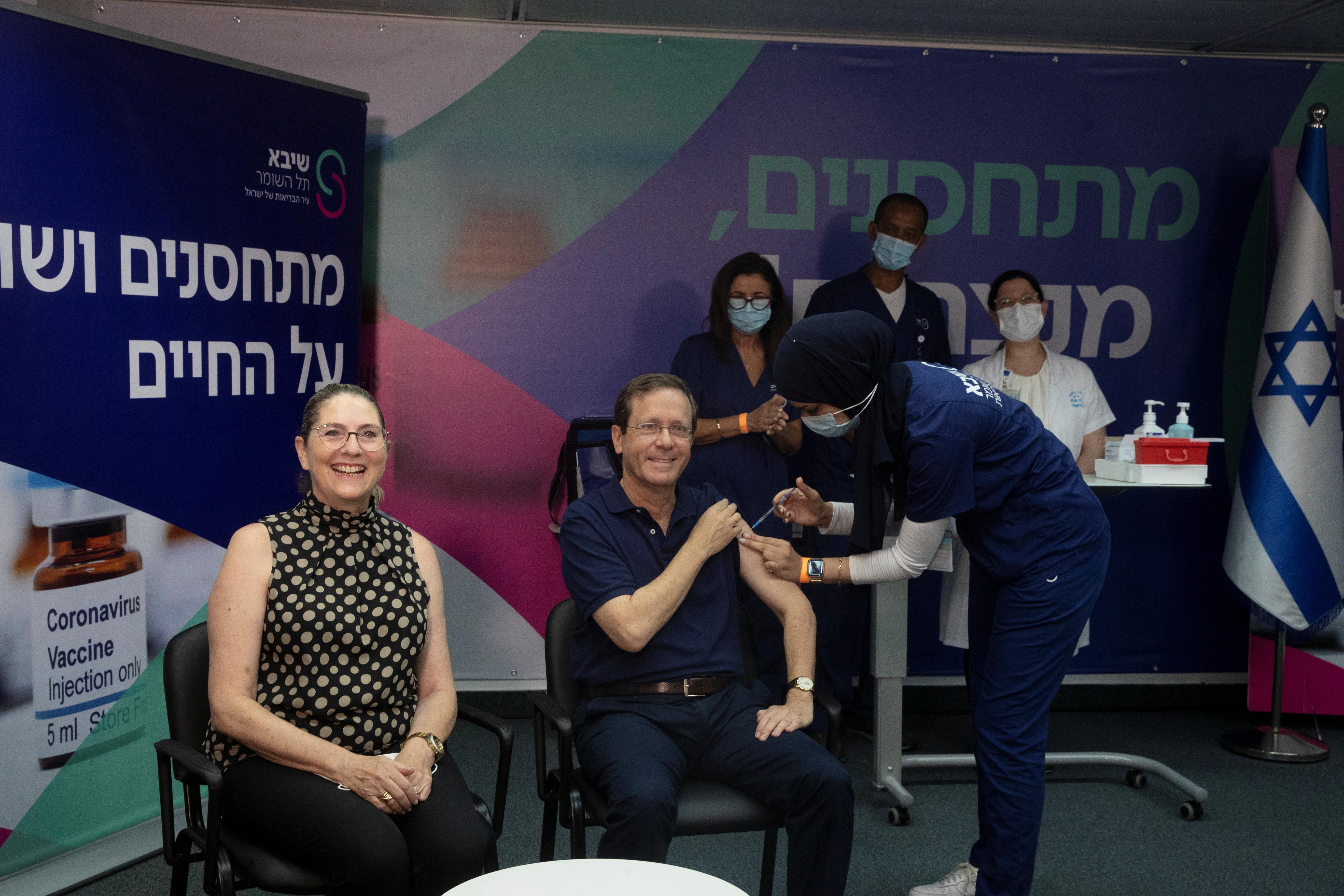 Israeli President Isaac Herzog receives a third dose of coronavirus disease (COVID-19) vaccine while his wife, Michal, reacts, at Sheba Medical Center in Ramat Gan, Israel, July 30, 2021. Maya Alleruzzo/Pool via REUTERS