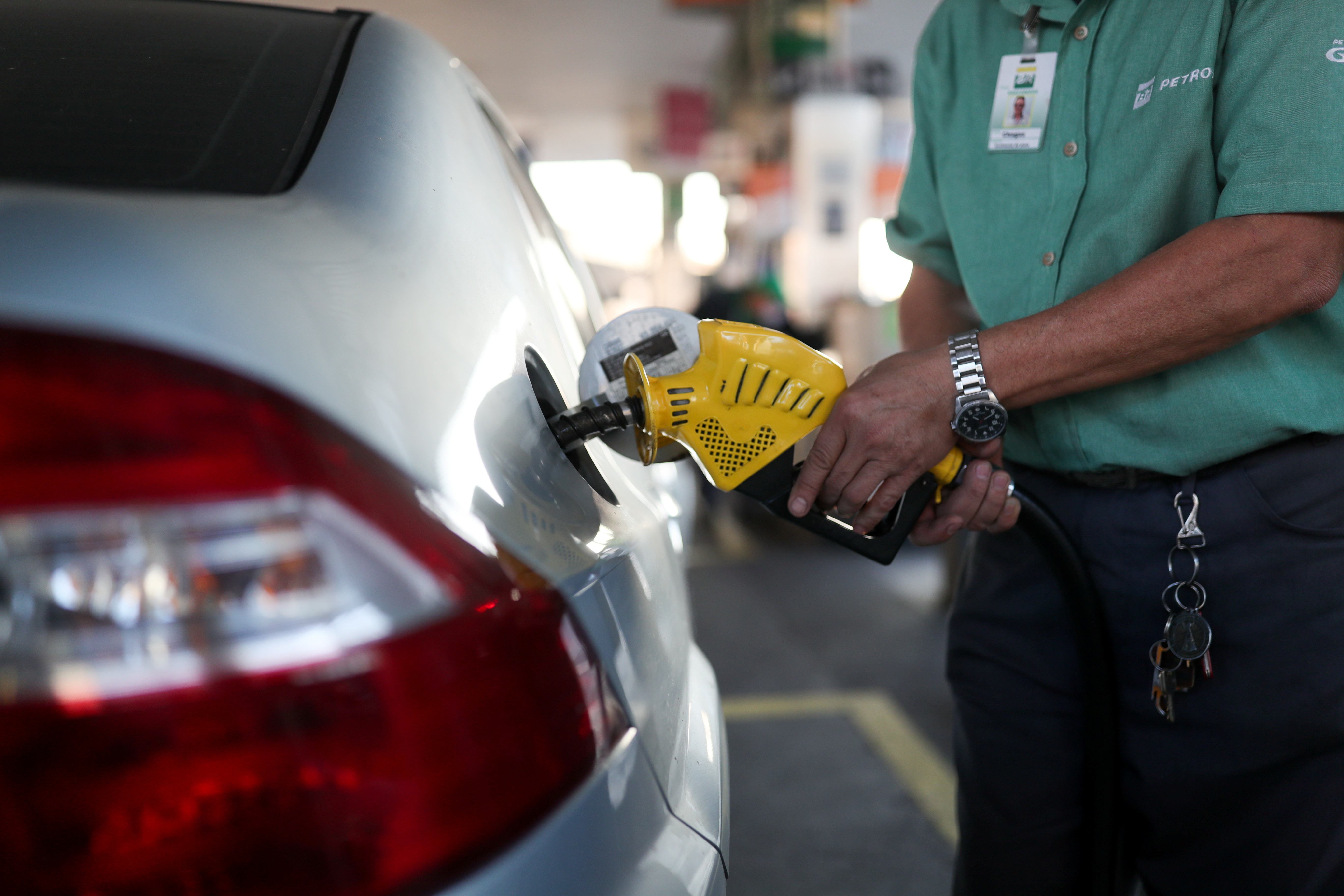 A man holds a fuel pump at a gas station in Rio de Janeiro, Brazil July 8, 2021. REUTERS/Amanda Perobelli/Files