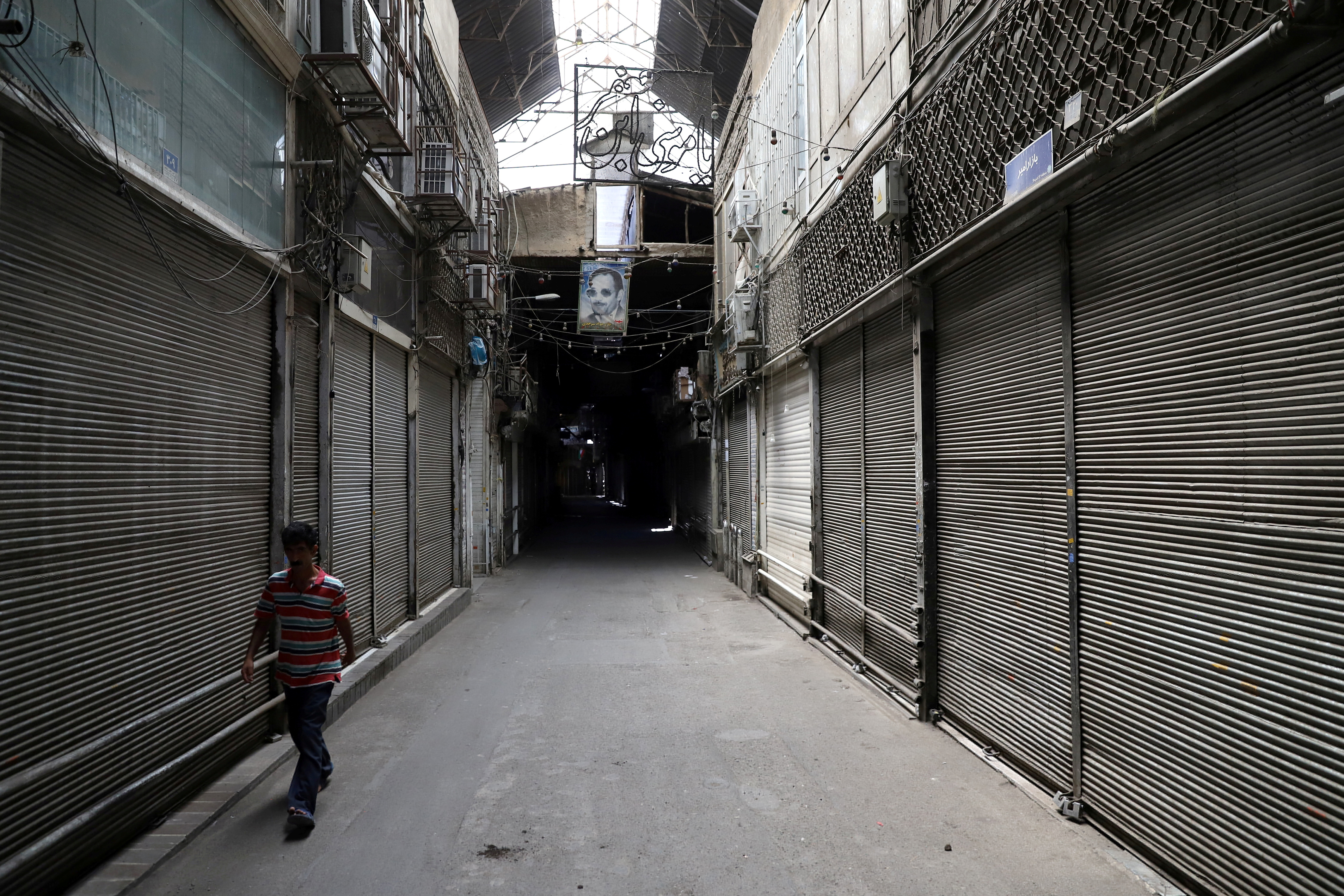 A man walks next to closed shops of Tehran Bazaar following the tightening of restrictions to curb the surge of the coronavirus disease (COVID-19) cases, in Tehran, Iran July 21, 2021. Majid Asgaripour/WANA (West Asia News Agency) via REUTERS