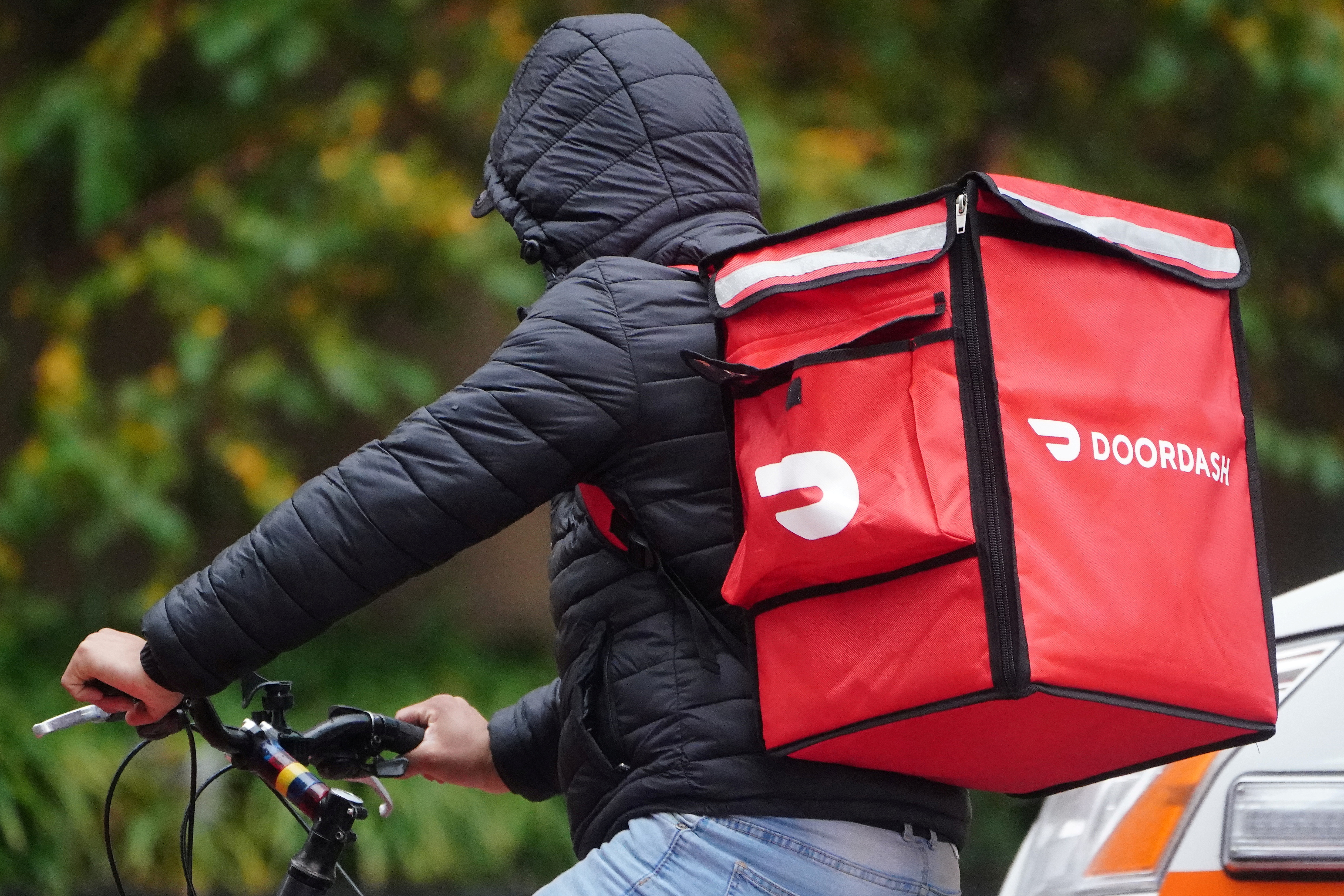 A delivery person for Doordash rides his bike in the rain in the Manhattan borough of New York City, New York, U.S., November 13, 2020. REUTERS/Carlo Allegri/File Photo