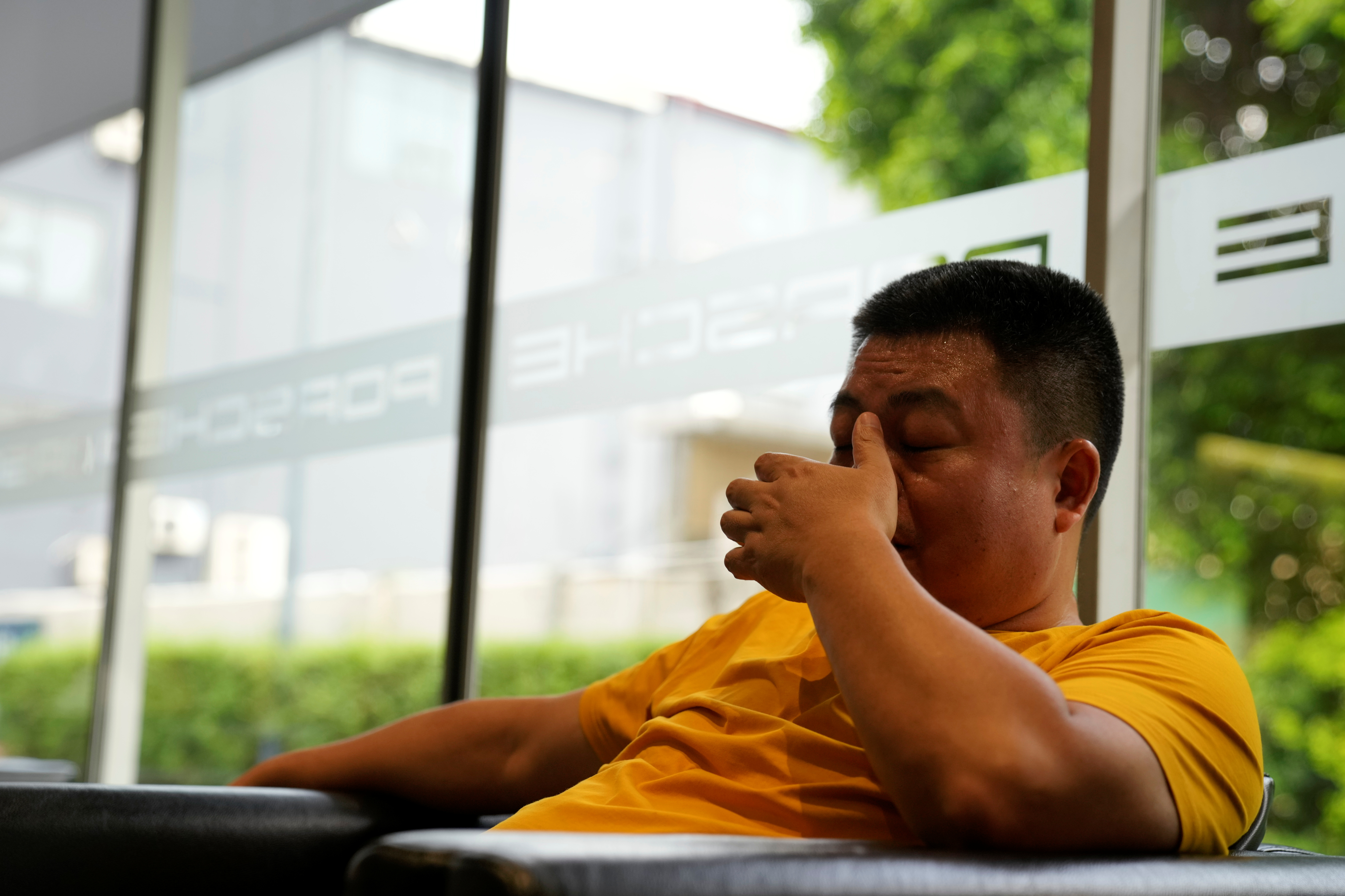 Guo Hui, whose cleaning business is owed money by China Evergrande Group, reacts as he waits at a car dealership to sell his Porsche Cayenne in order to pay his debts, in Guangzhou, Guangdong province, China September 27, 2021. Picture taken September 27, 2021. REUTERS/Aly Song