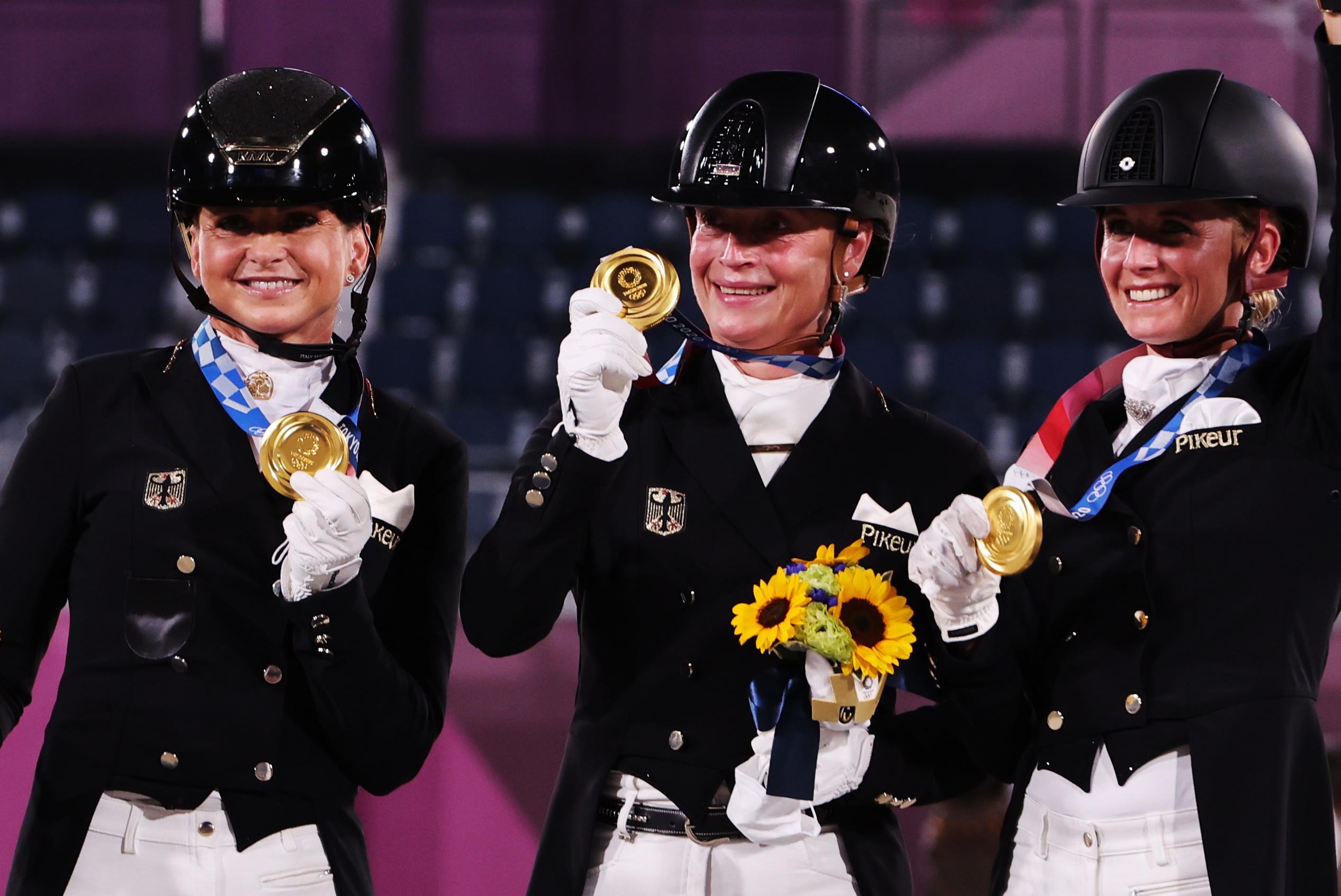 Tokyo 2020 Olympics - Equestrian - Dressage - Team - Medal Ceremony - Equestrian Park - Tokyo, Japan - July 27, 2021. Gold medallists Dorothee Schneider of Germany, Isabell Werth of Germany and Jessica von Bredow-Werndl of Germany celebrate on the podium. REUTERS/Alkis Konstantinidis