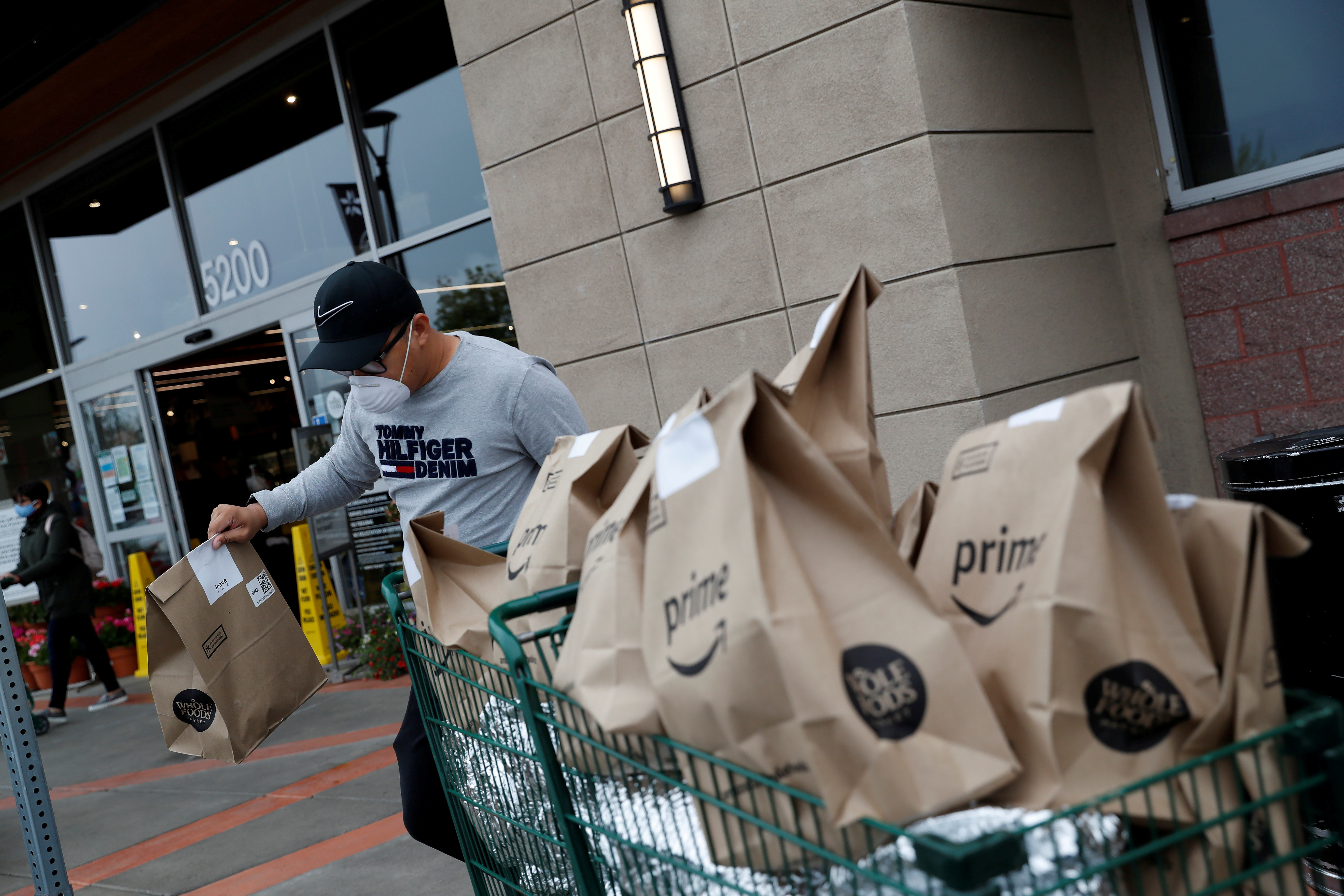 Excelso Sabulau, a 35-year-old independent contract delivery driver for Amazon Flex, wears a protective mask as he carries deliveries to his car near a Whole Foods Market, as spread of the coronavirus disease (COVID-19) continues, in Dublin, California, U.S., April 6, 2020. REUTERS/Shannon Stapleton/File Photo