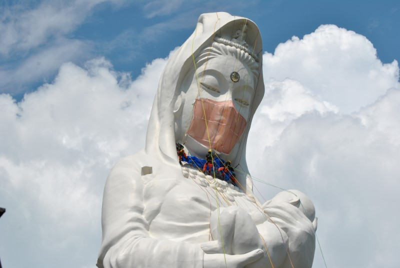 Workers place a mask on a 57-metre-high statue of Buddhist goddess Kannon to pray for the end of the coronavirus disease (COVID-19) pandemic at Houkokuji Aizu Betsuin temple in Aizuwakamatsu, Fukushima Prefecture, Japan in this handout photo taken on June 15 2021. Houkokuji Aizu Betsuin/Handout via REUTERS