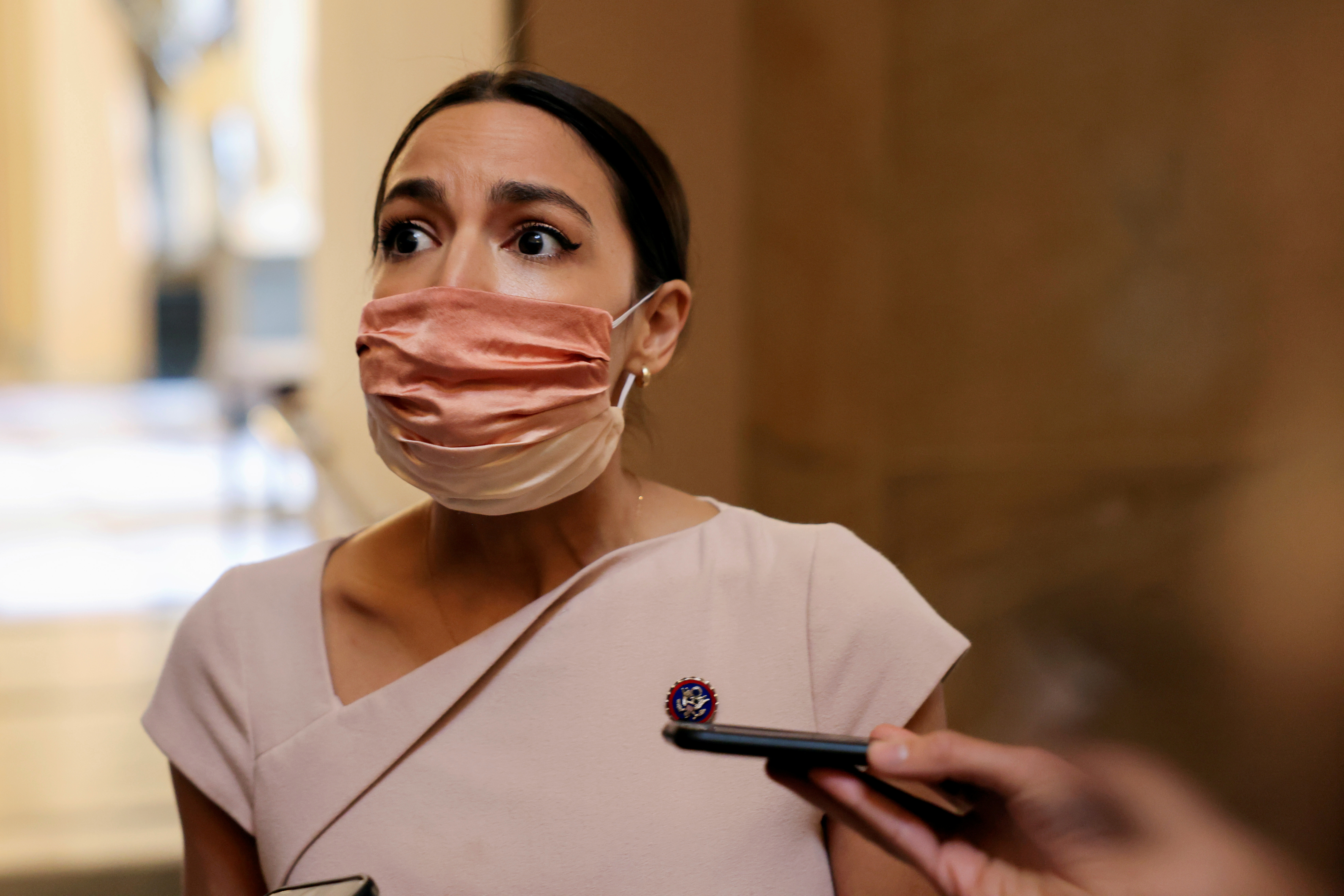 U.S. Representative Alexandria Ocasio-Cortez reacts as she walks past reporters on Capitol Hill in Washington, U.S., May 13, 2021. REUTERS/Evelyn Hockstein/File Photo