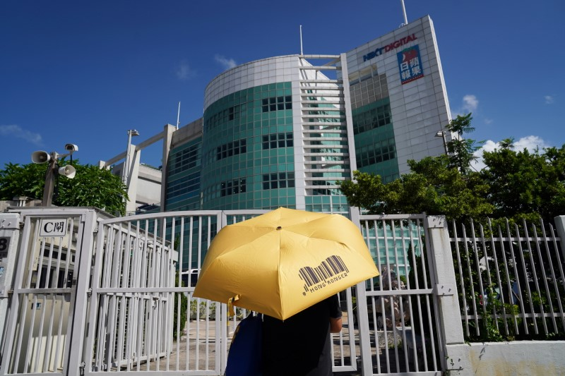 A supporter holding an umbrella stands in front of the entrance to the offices of Apple Daily and Next Media after police raided the newsroom, in Hong Kong, China June 17, 2021. REUTERS/Lam Yik