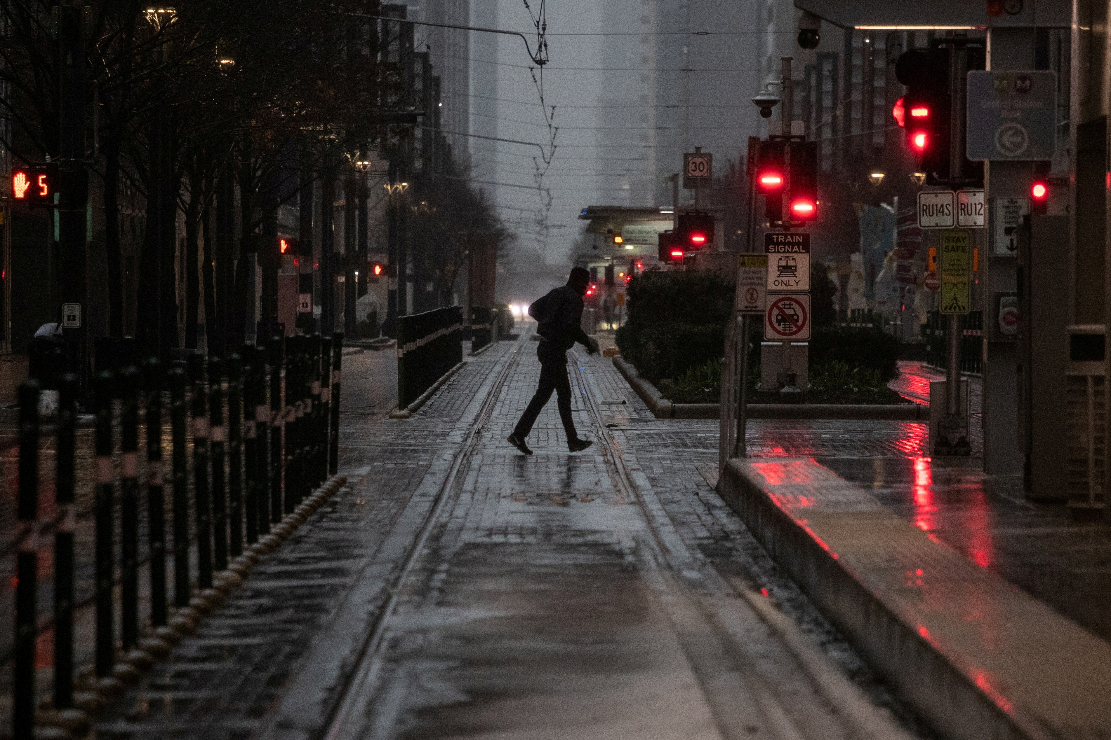 A man crosses Main Street in downtown during record-breaking temperatures in Houston, U.S., February 17, 2021. REUTERS/Adrees Latif/File Photo